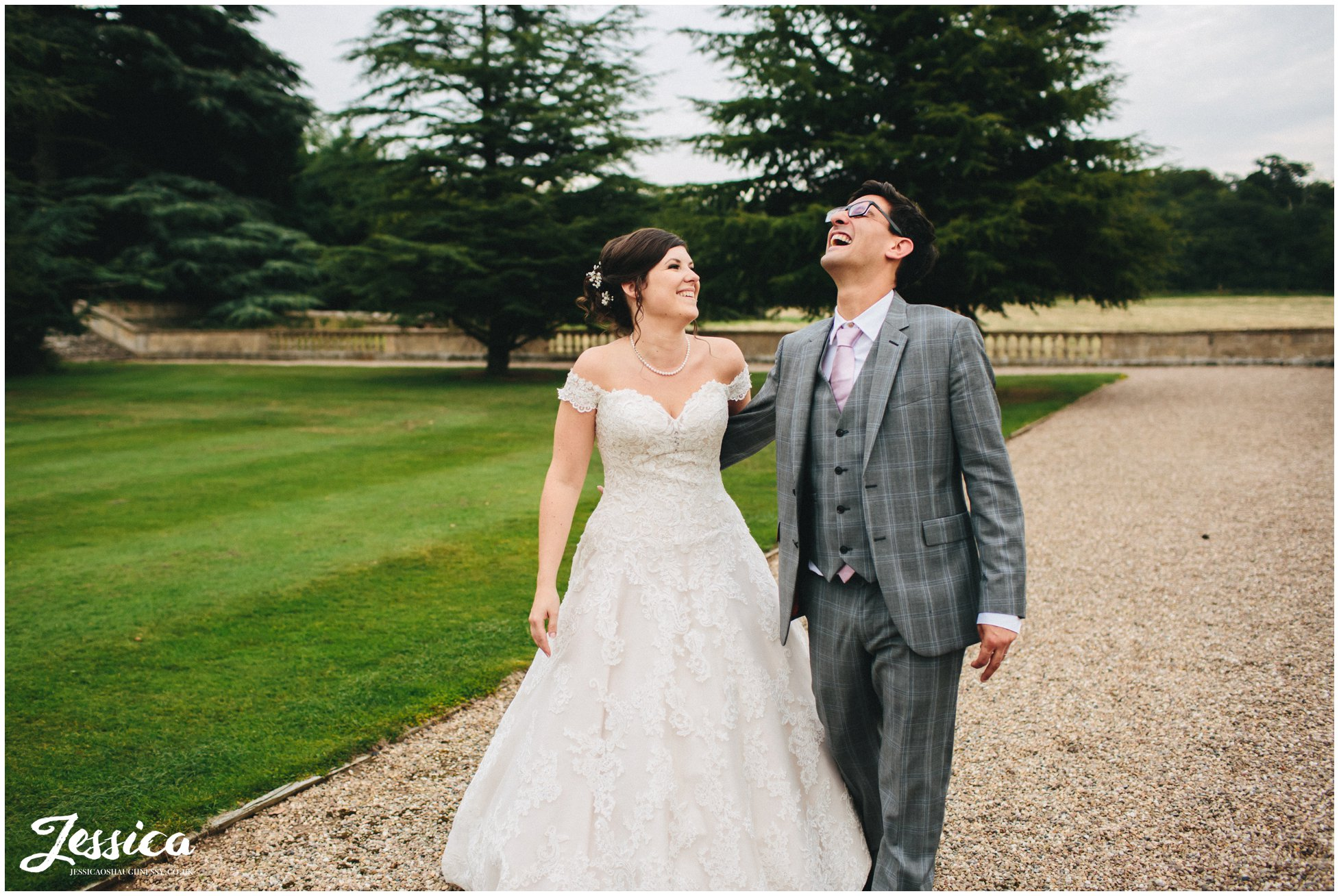 bride and groom walk through prestwold hall laughing