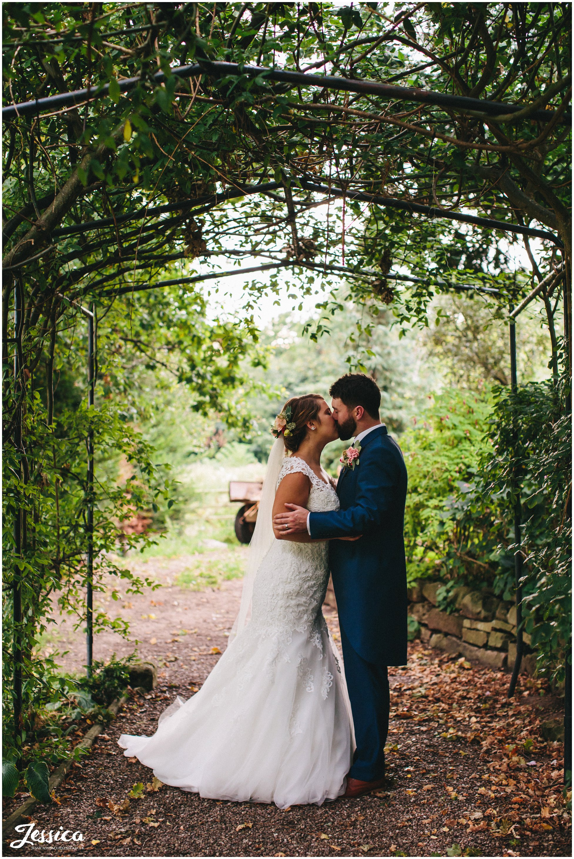 willington hall wedding - couple kiss under archway