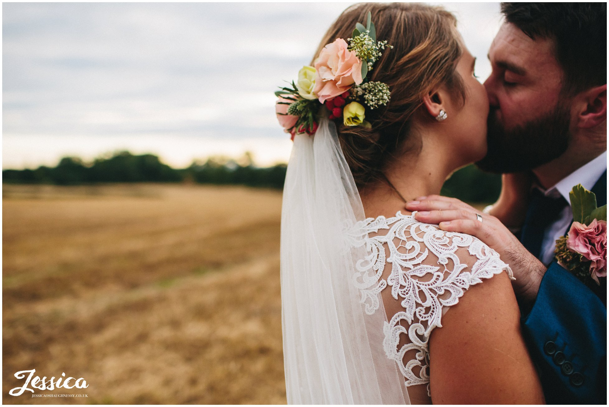 couple kissing as bride wears floral headpiece