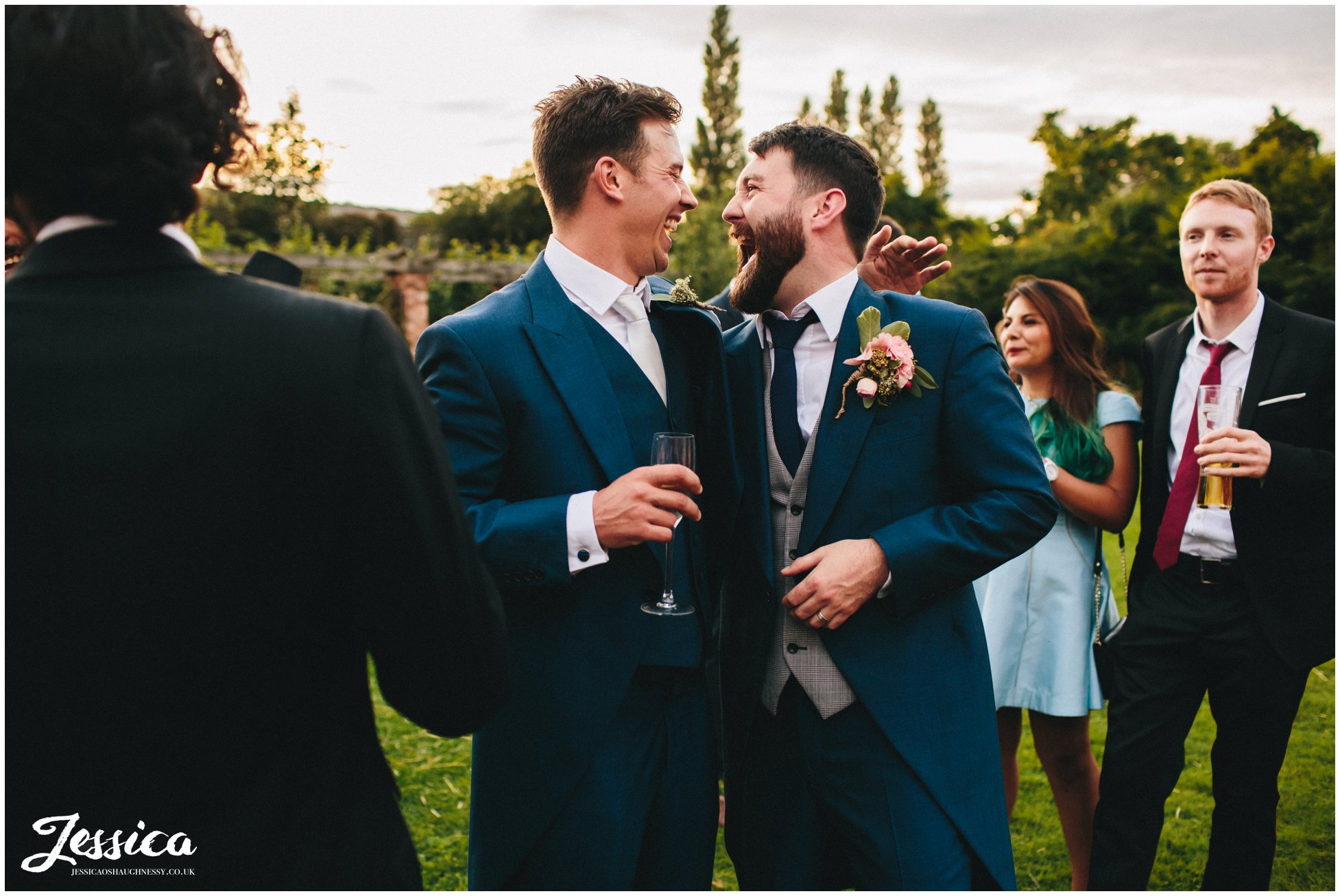 groom and best man hug during a willington hall wedding reception
