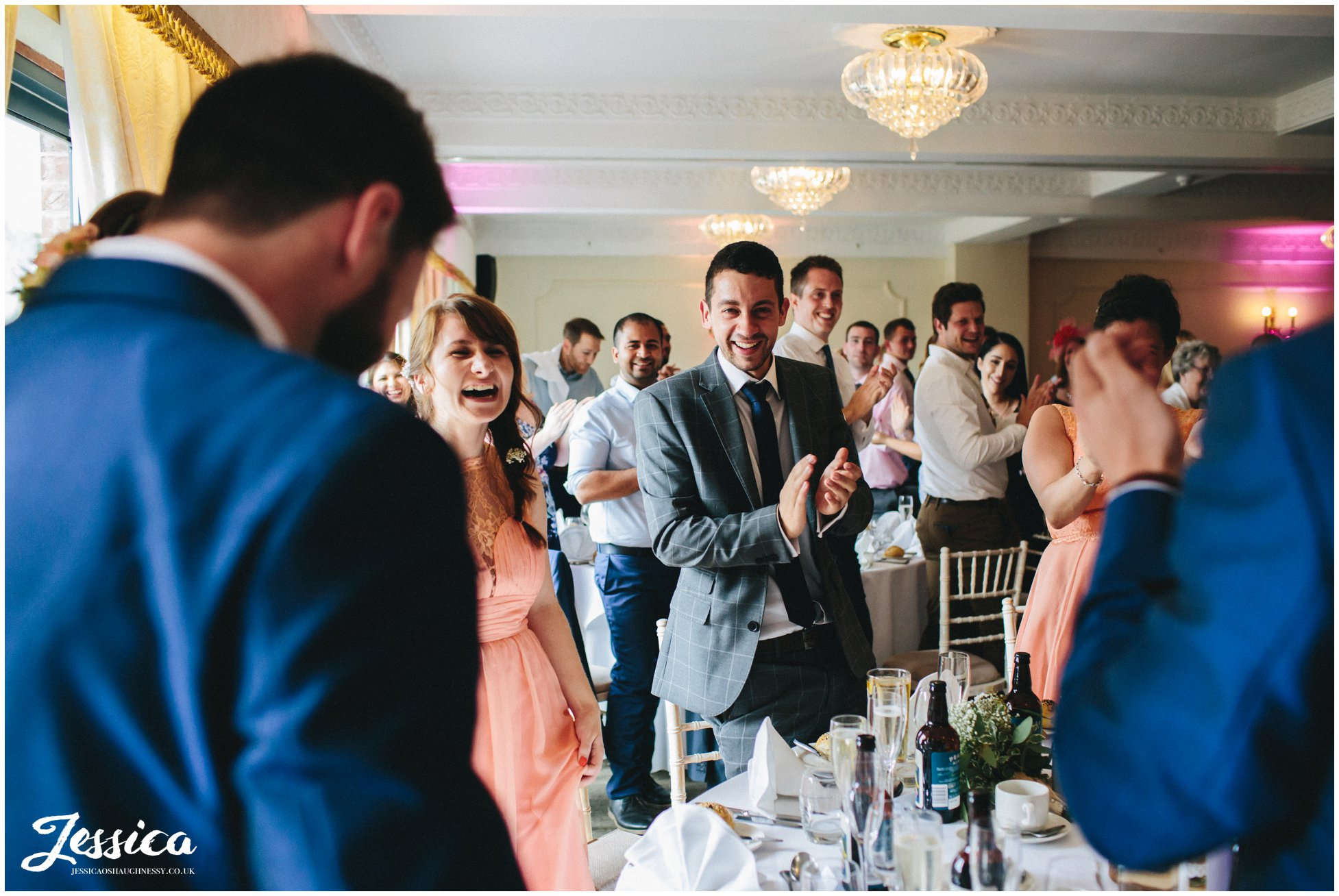 friends and family clap as newly weds enter