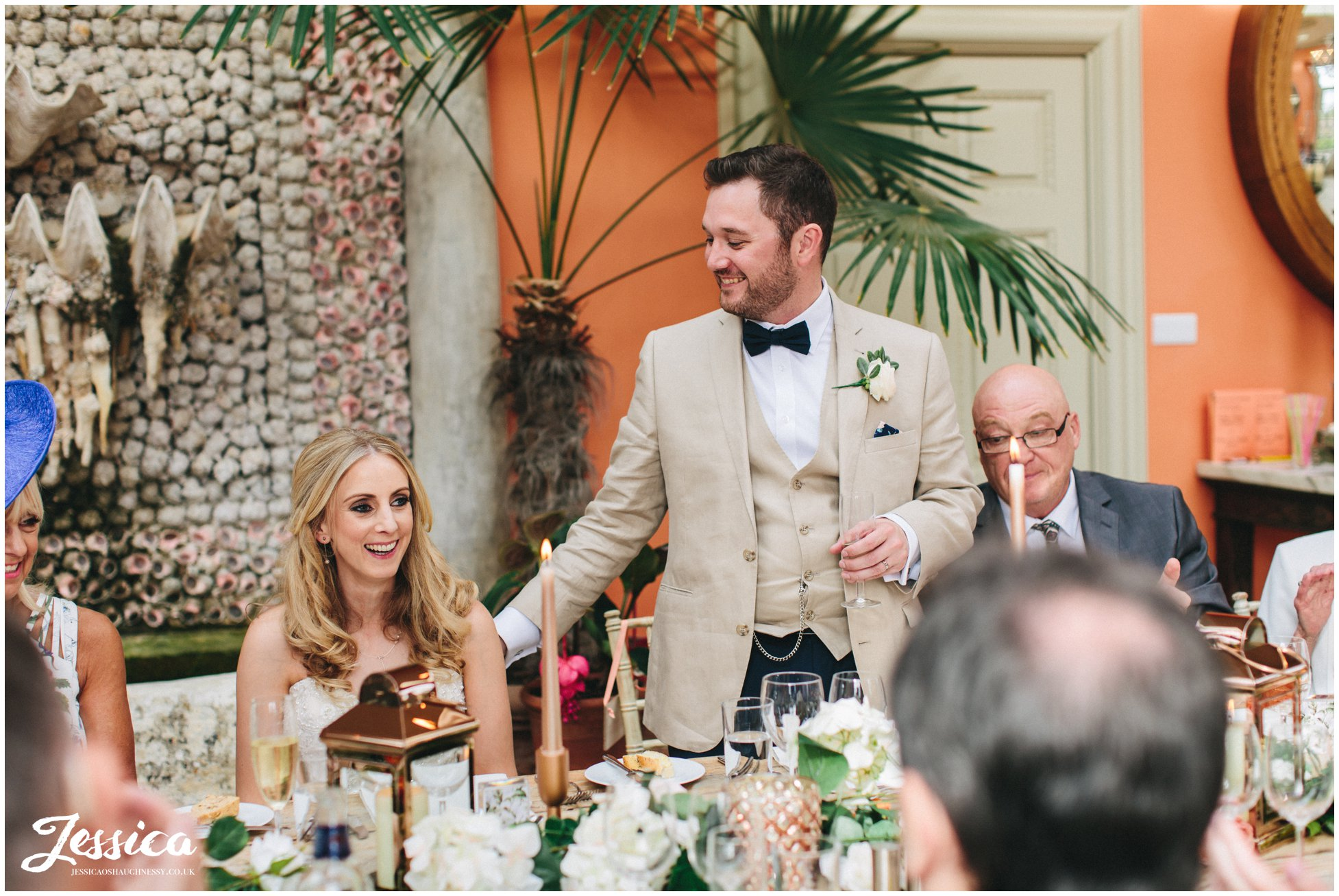 groom stands to give speech on his wedding day at the lost orangery
