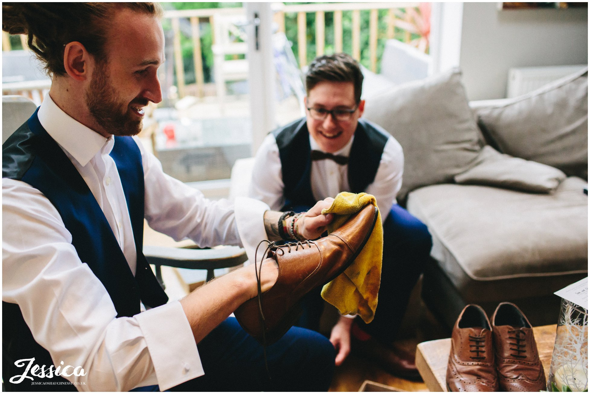 groomsmen polish their shoes before the wedding