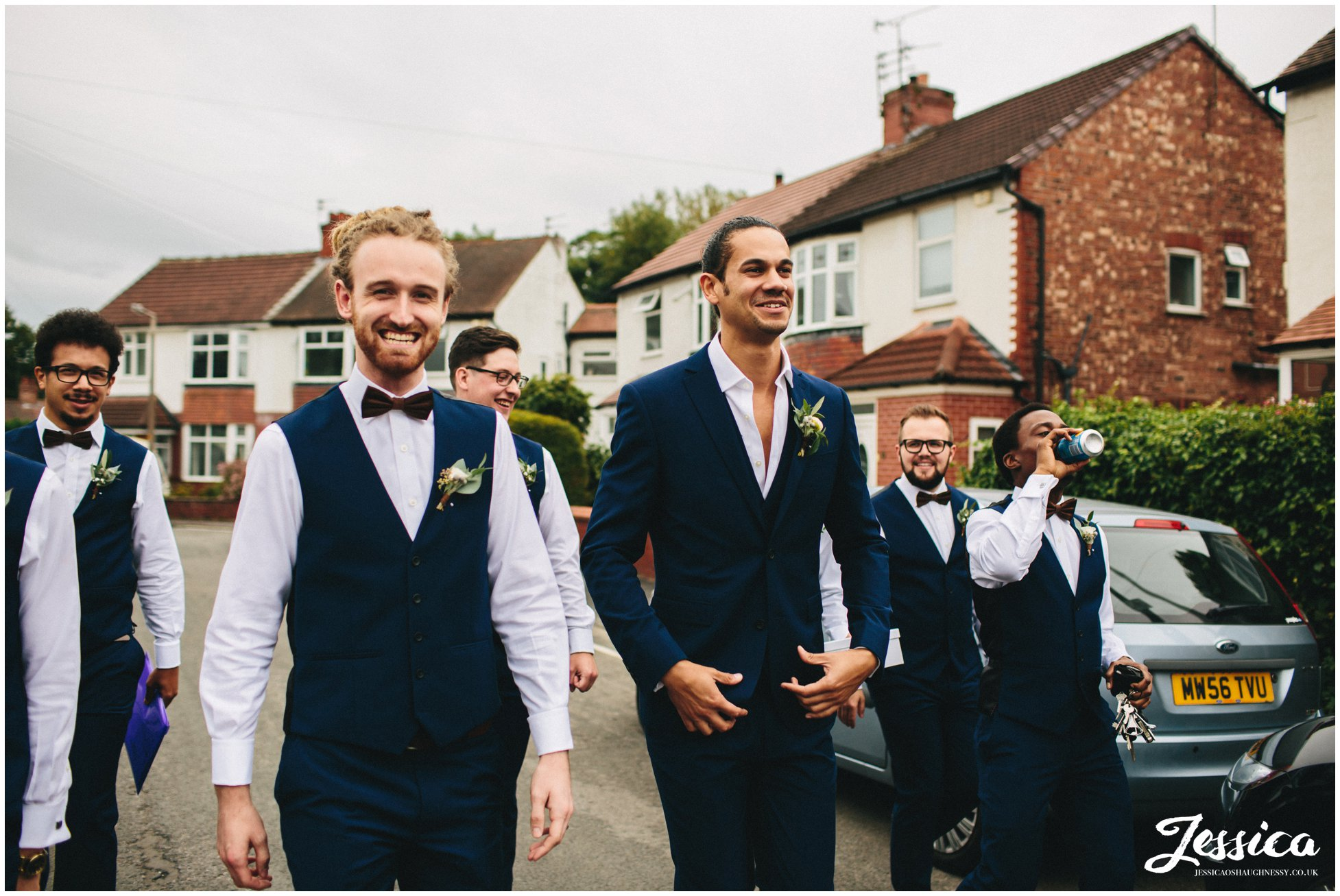 groomsmen walk down the road to the church in cheadle