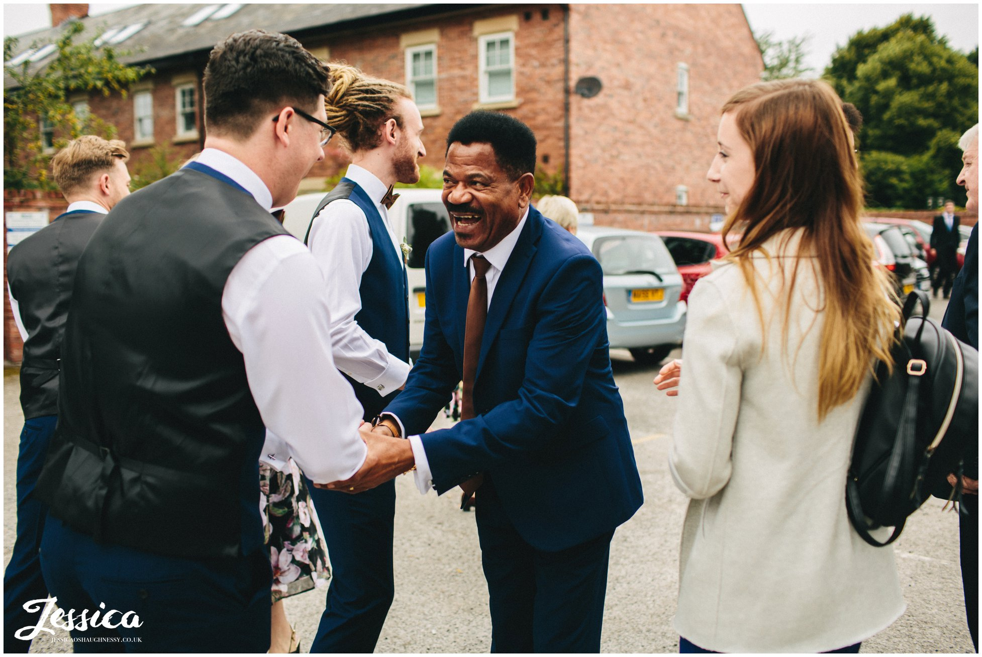 father of the groom shakes hands with arriving guests