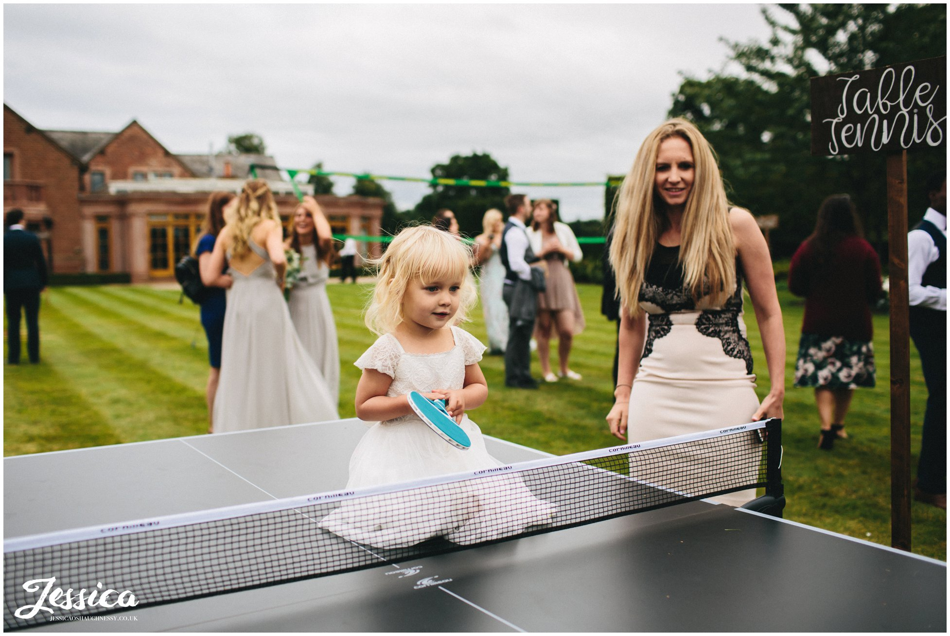 child sits on ping pong table so she can reach
