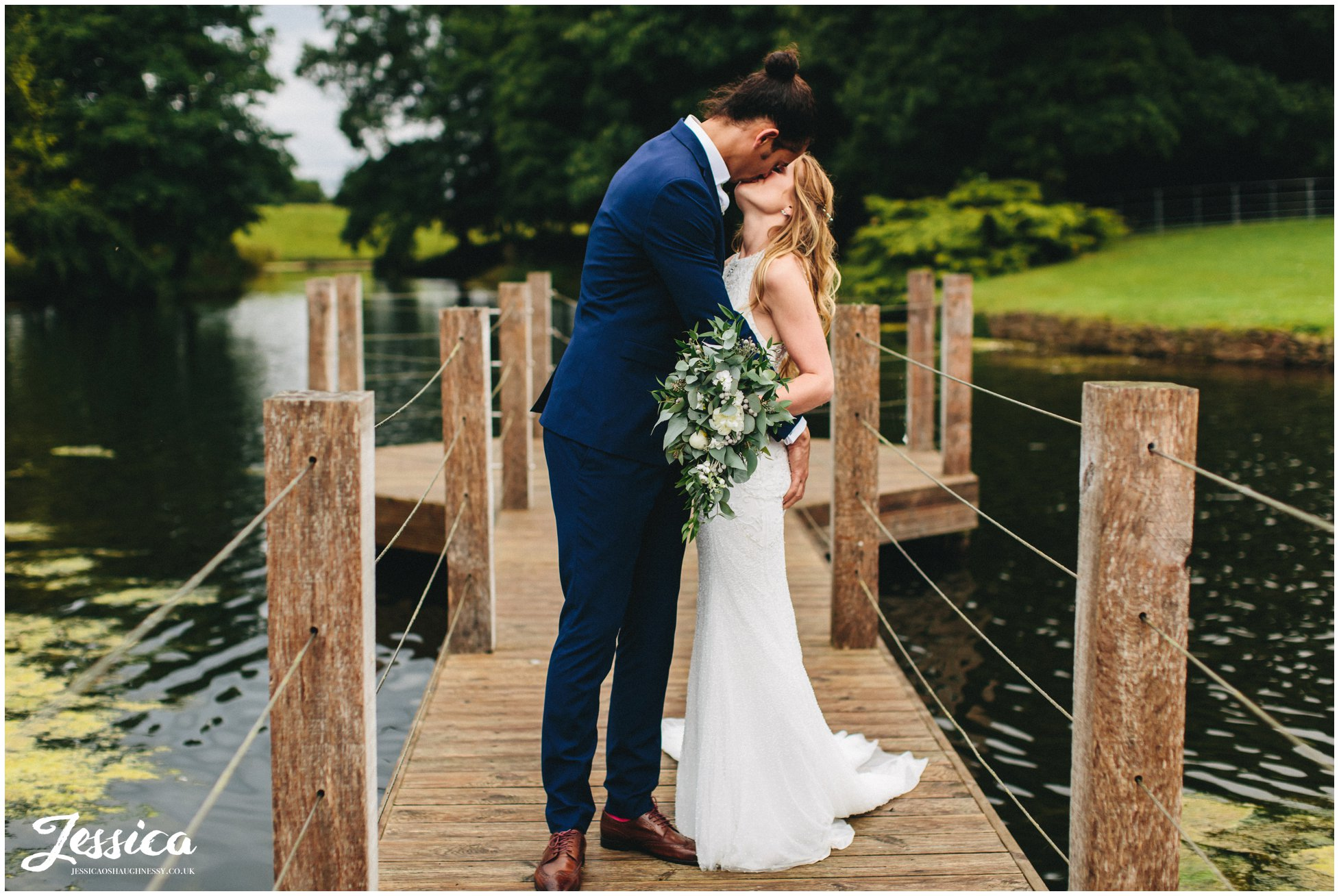newly wed's kiss on the jetty at merrydale manor in cheshire