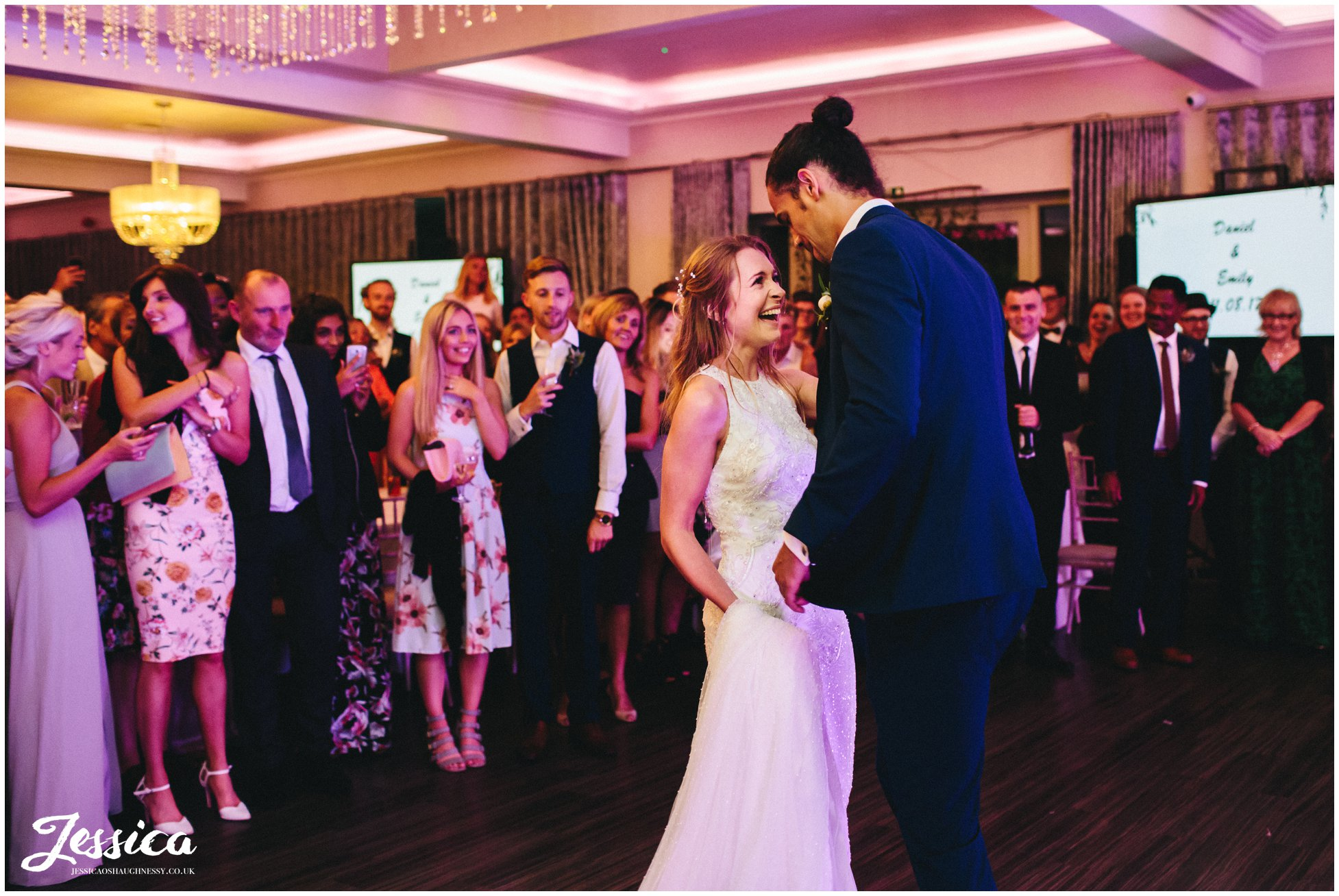bride giggles during their first dance as husband and wife