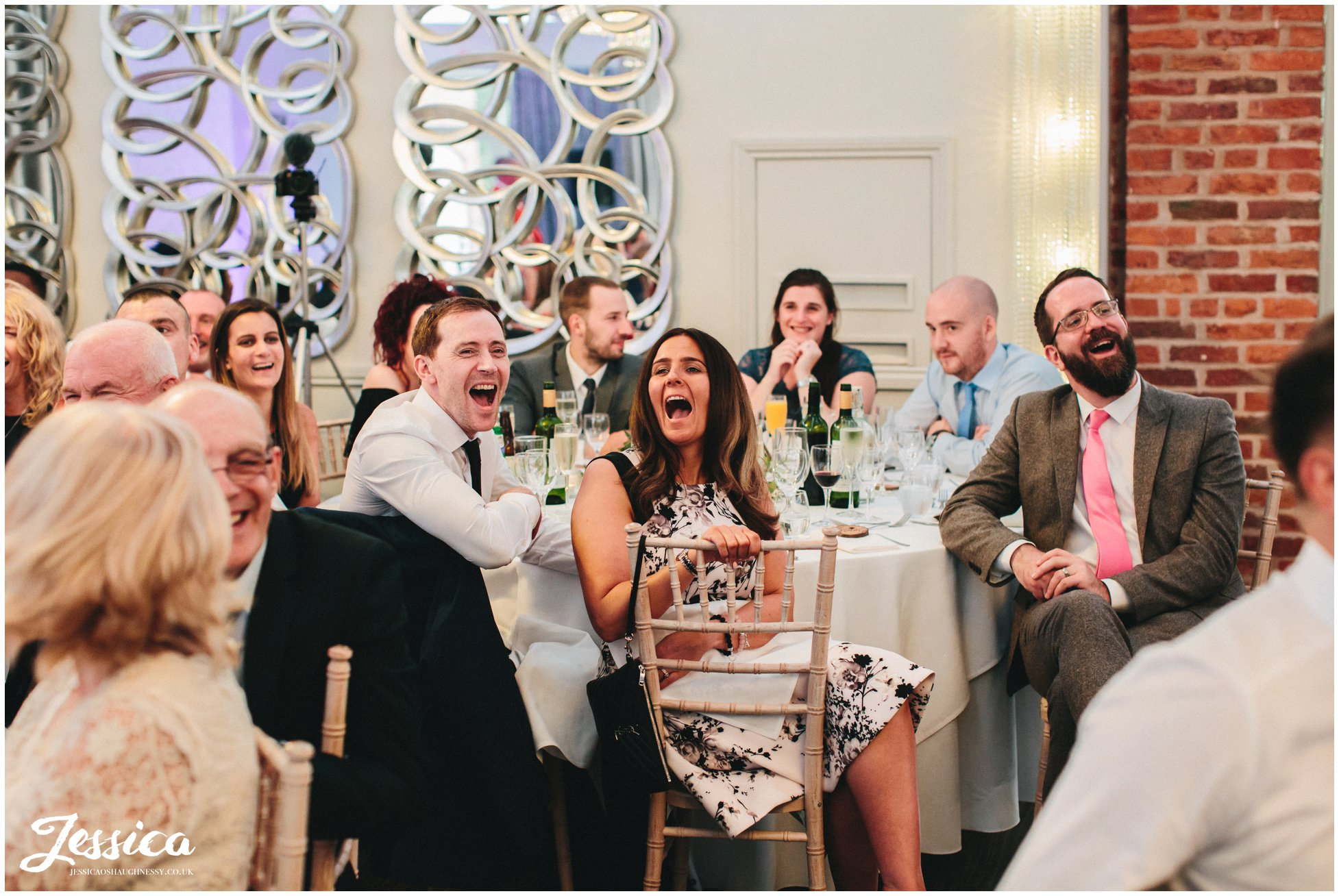 guests laughing during the grooms speech at merrydale manor in cheshire