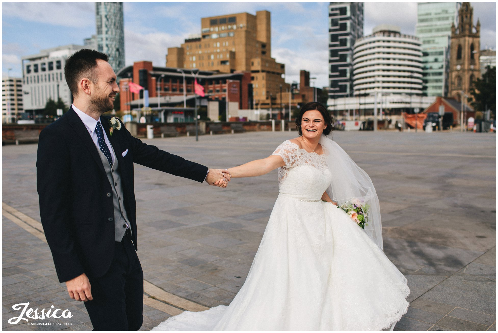 couple walk holding hands along the waterfront in liverpool