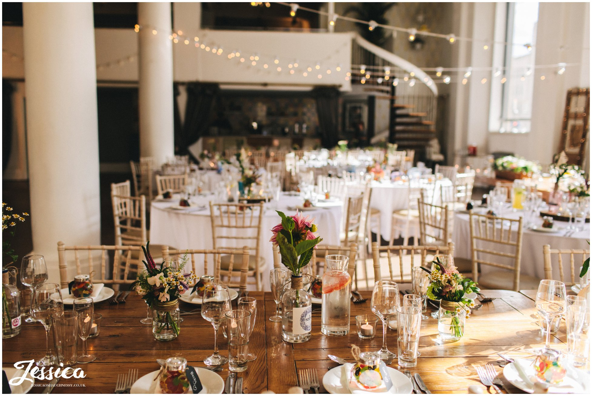 flowers in gin bottles decorate the tables at oh me oh my - a liverpool wedding venue