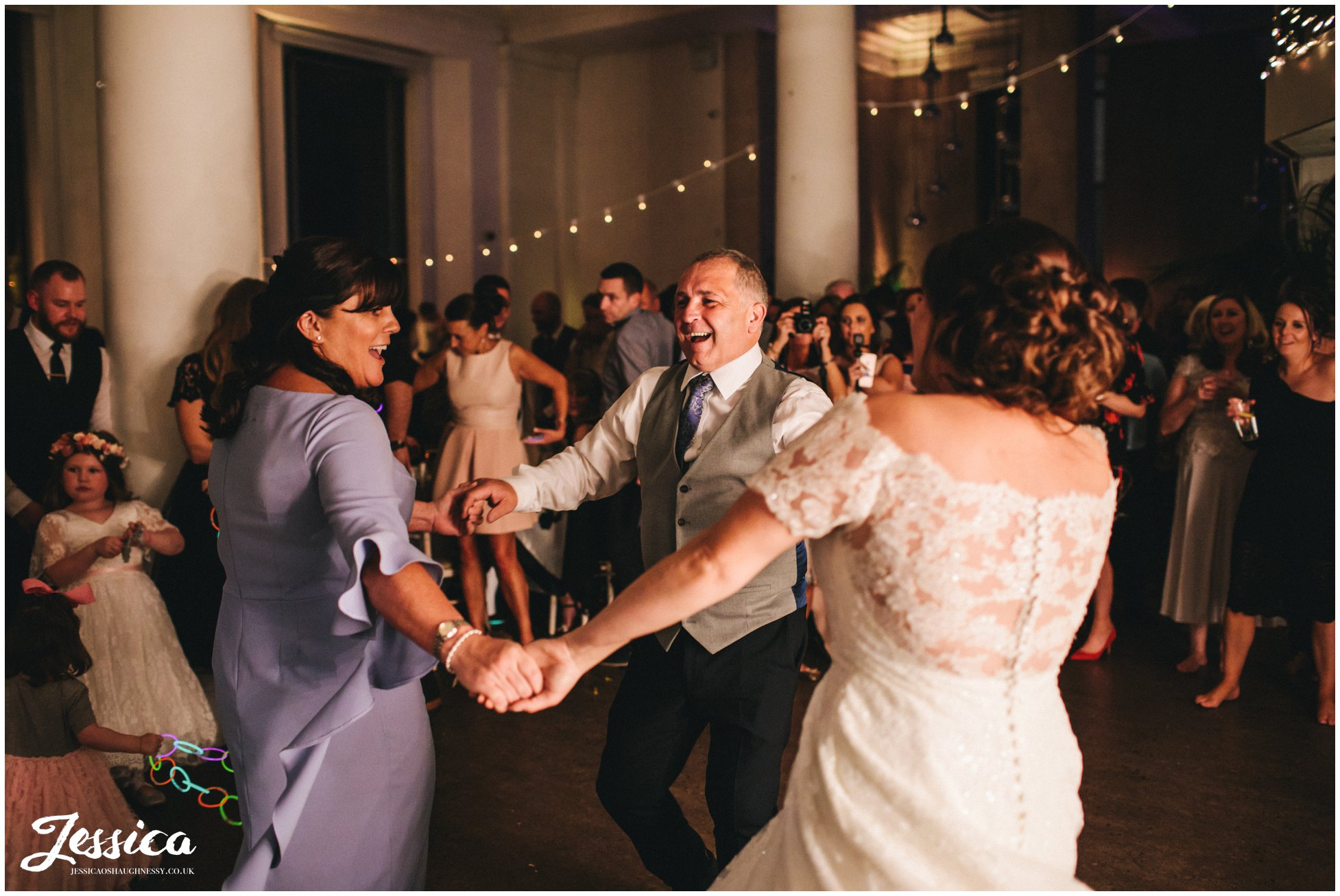bride dances with mum and dad during her wedding reception