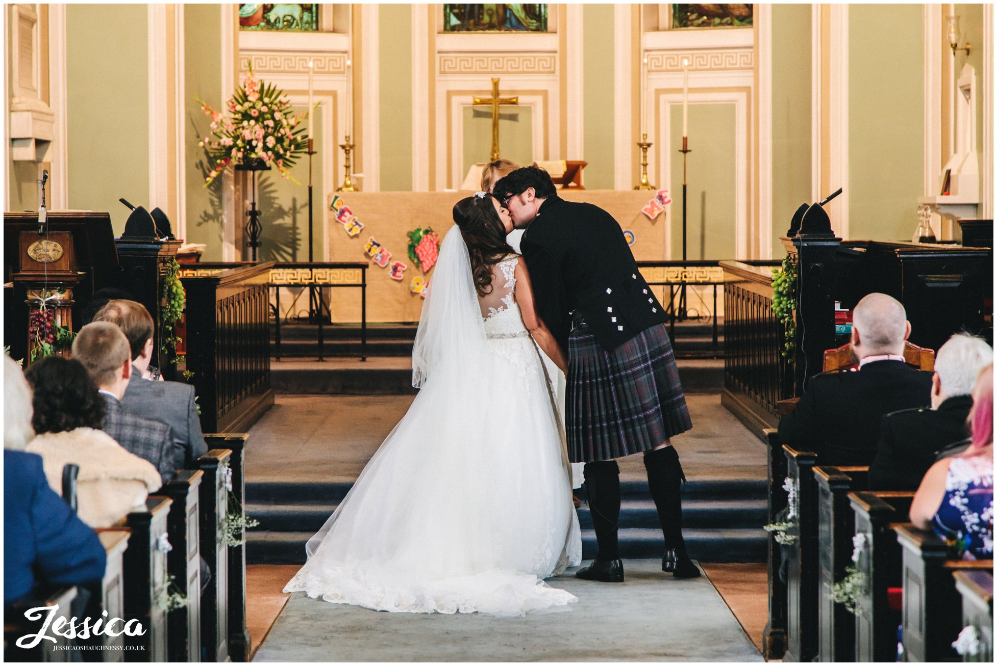 bride and groom share first kiss at the church alter