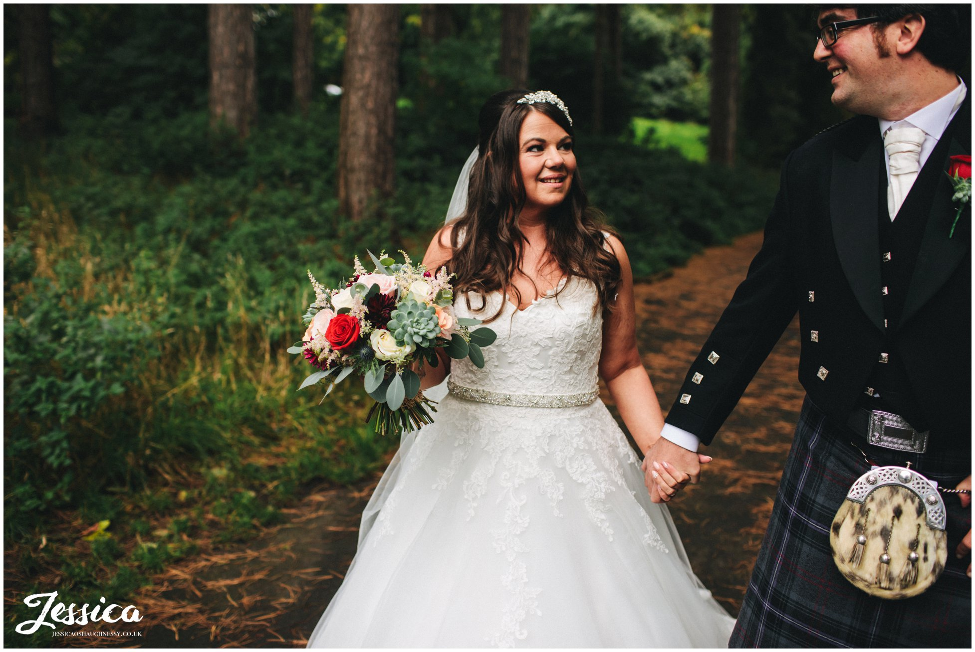 bride and groom walk through woodland at sefton park in liverpool