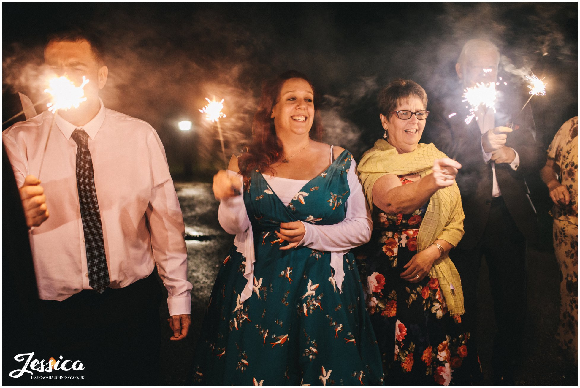 guests hold sparklers to light bride and groom
