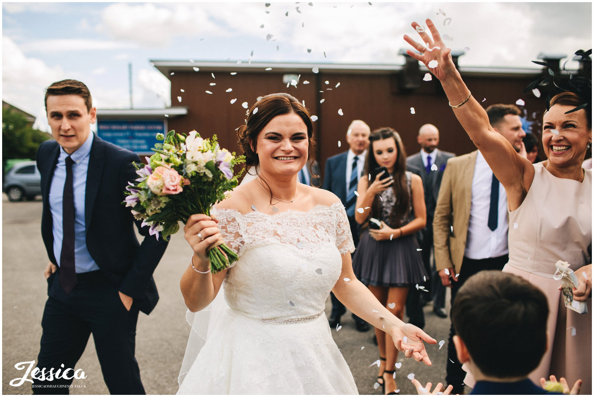 guests throw confetti over the bride