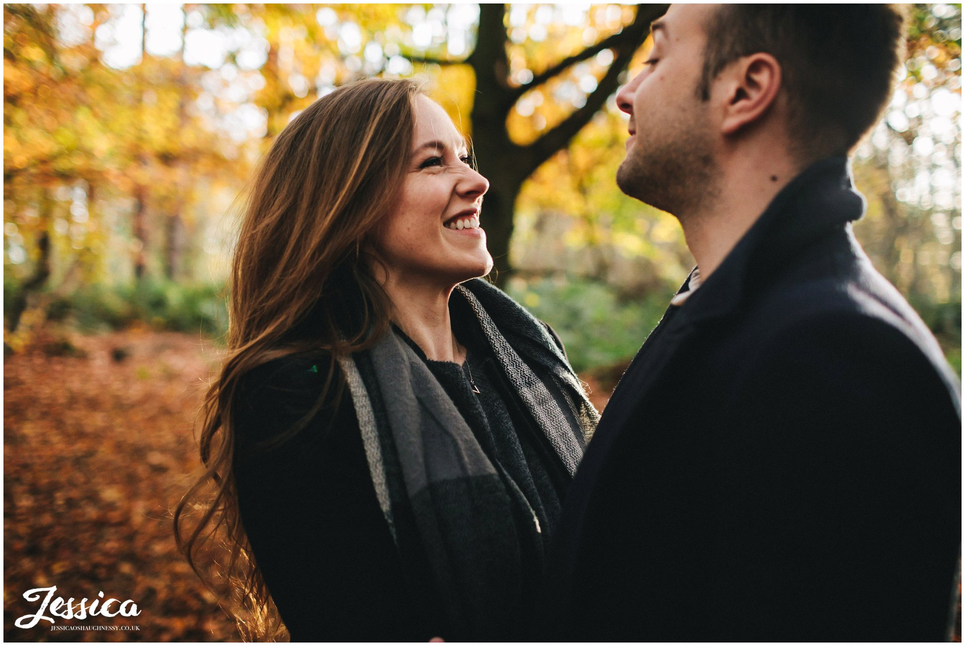 girl smiles at fiance during their forest engagement shoot