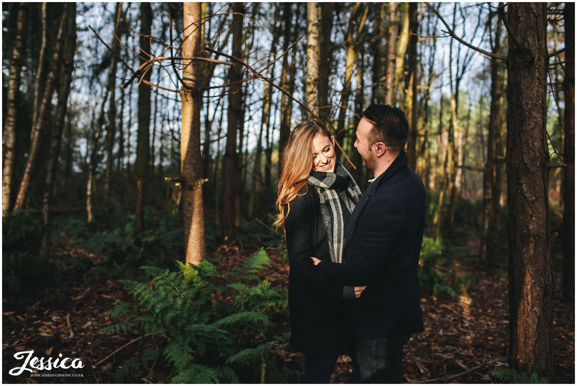 couple embrace in the trees at delamere forest in cheshire