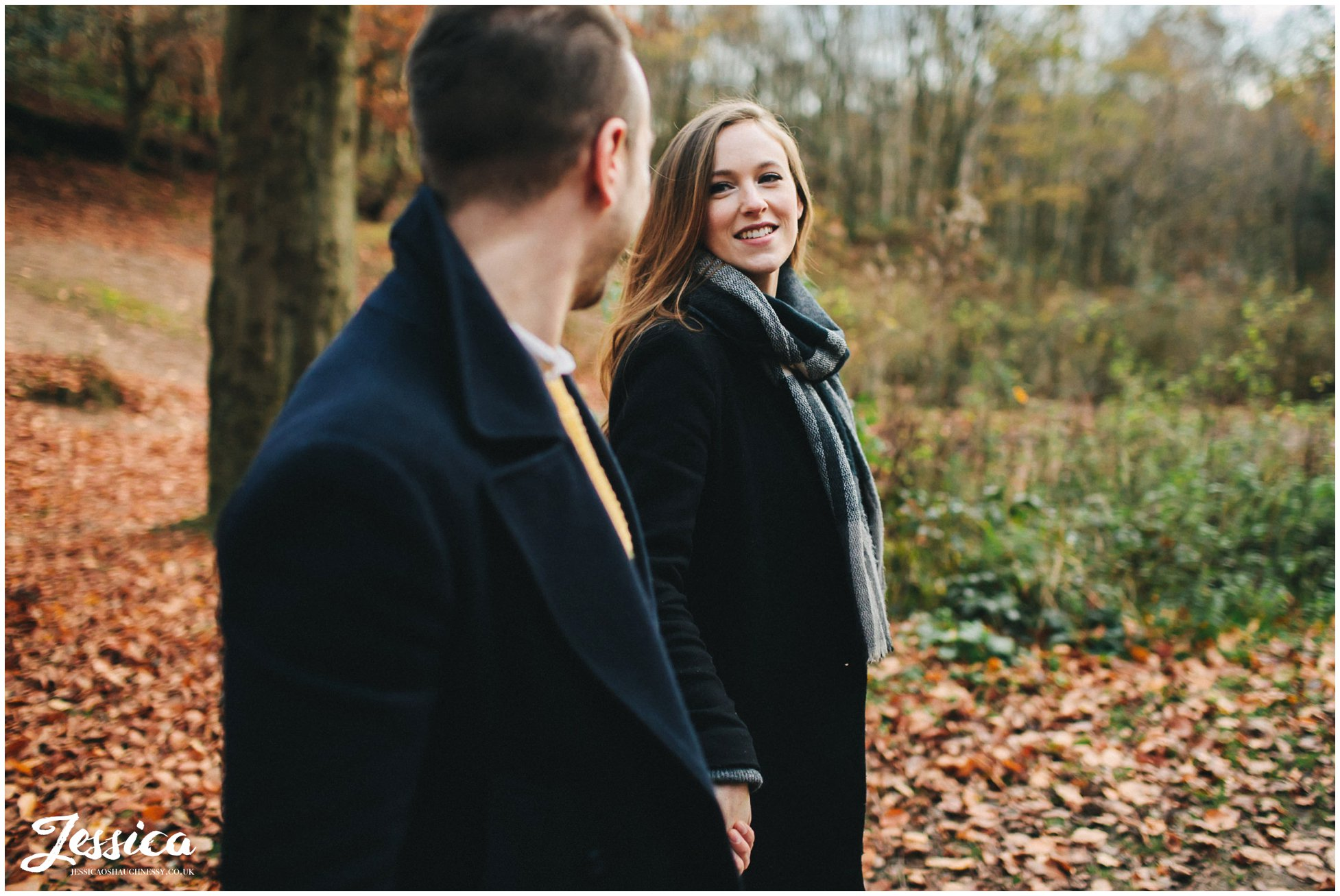 newly engaged couple hold hands walking through delamere forest in cheshire