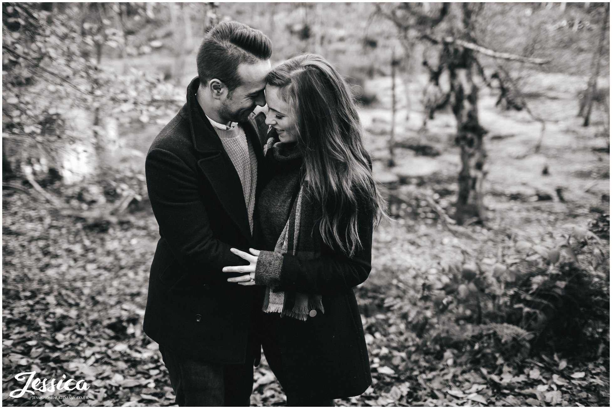 black and white shot of engaged couple embracing - delamere forest in cheshire