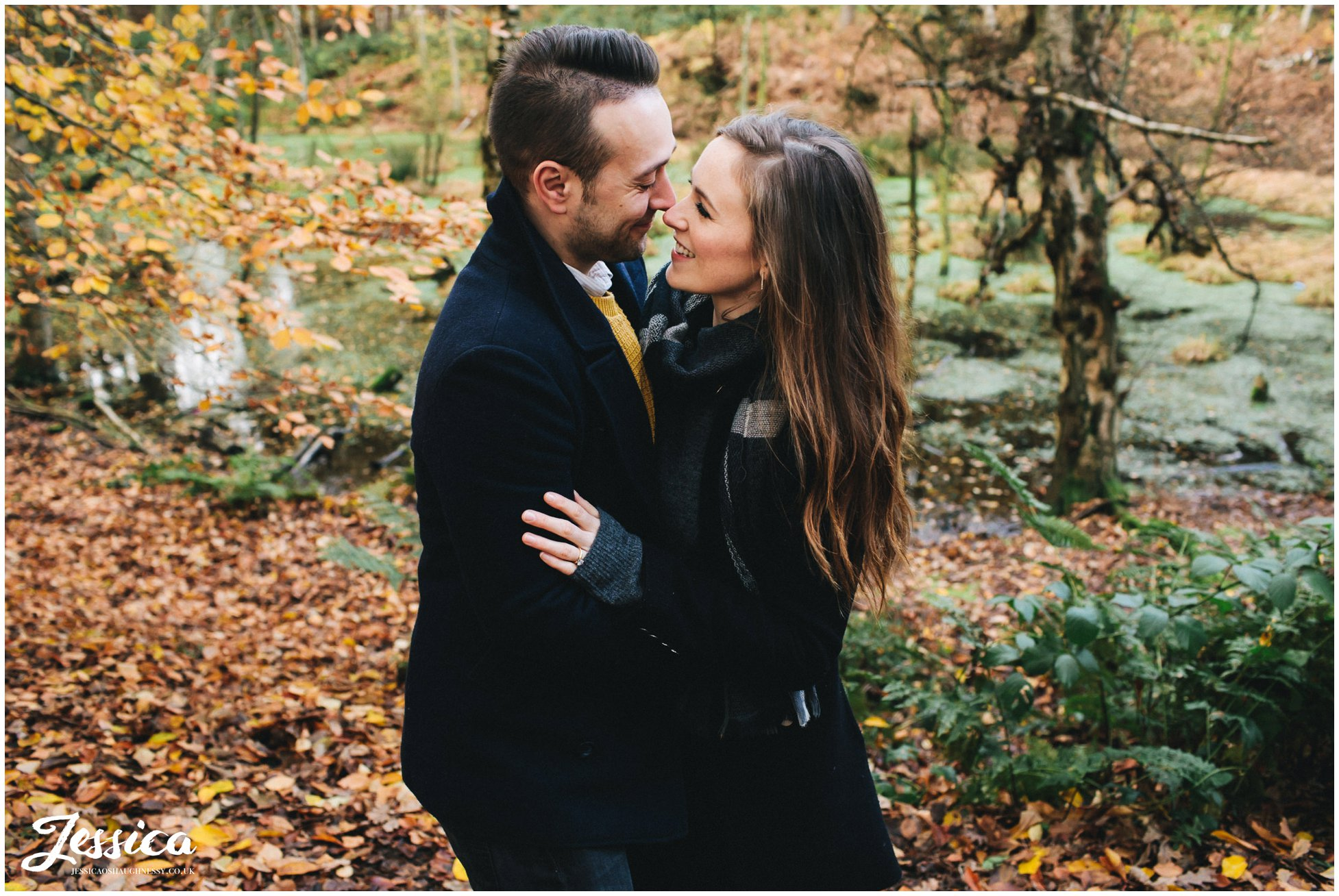 couple embracing in front of the lake at delamere forest in cheshire