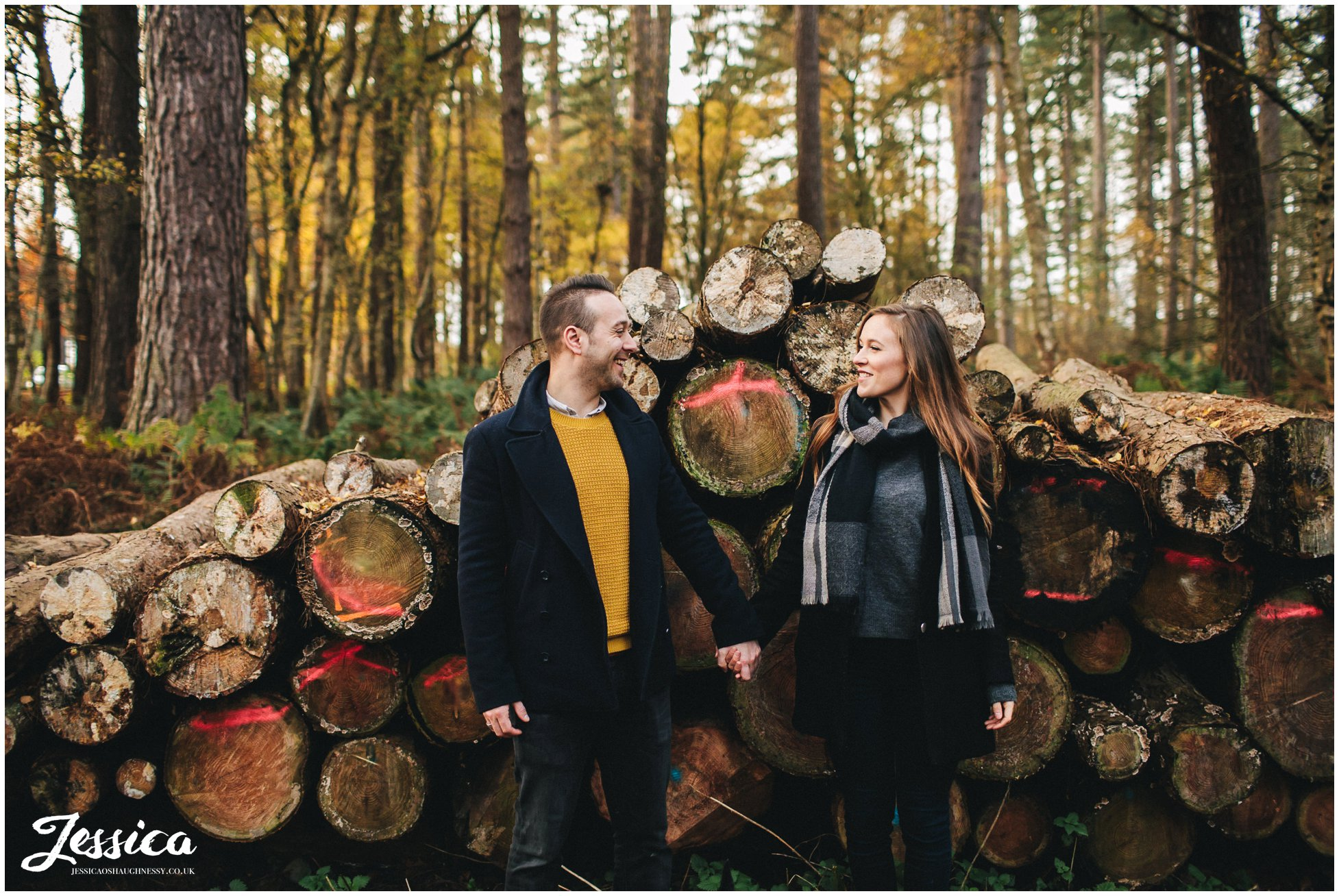 couple hold hands in front of cut logs, a cheshire engagement shoot