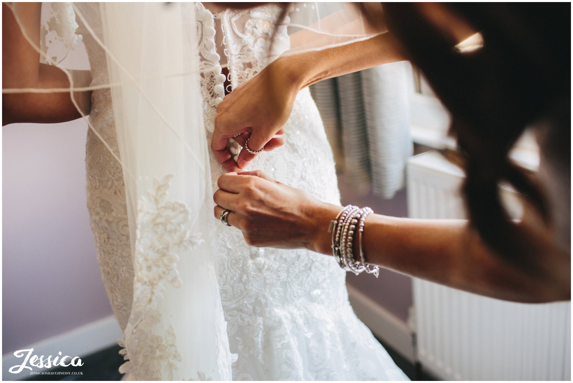 maid of honour fastens brides dress