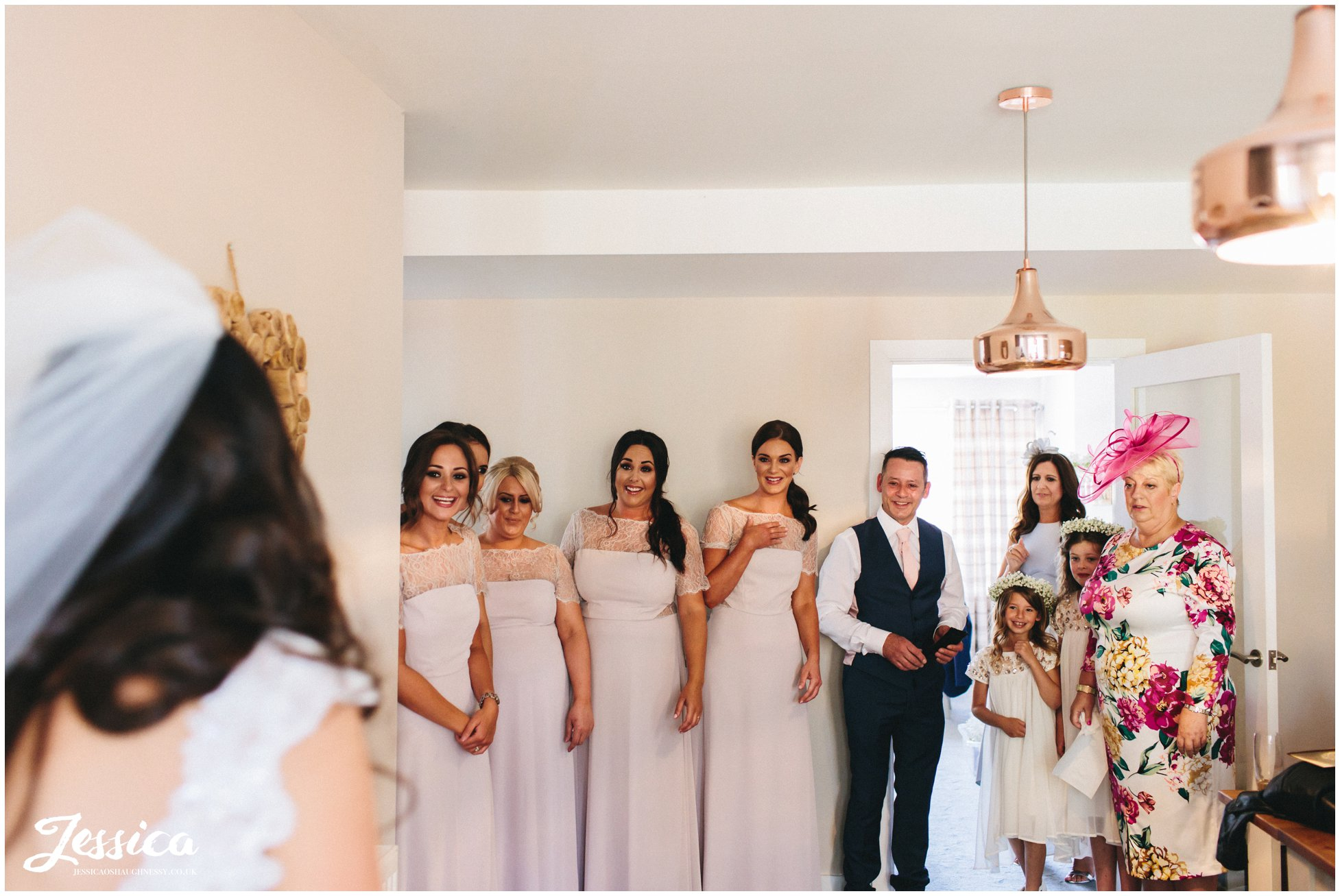 bride walks downstairs revealing her dress to friends & family