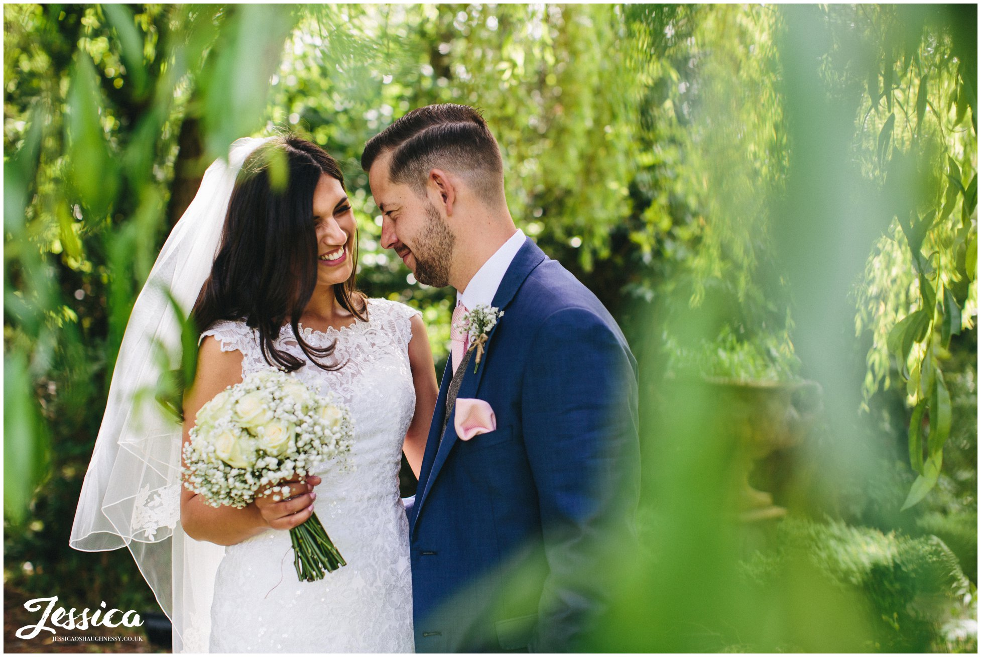 newly wed's smiling at each other under the willow tree