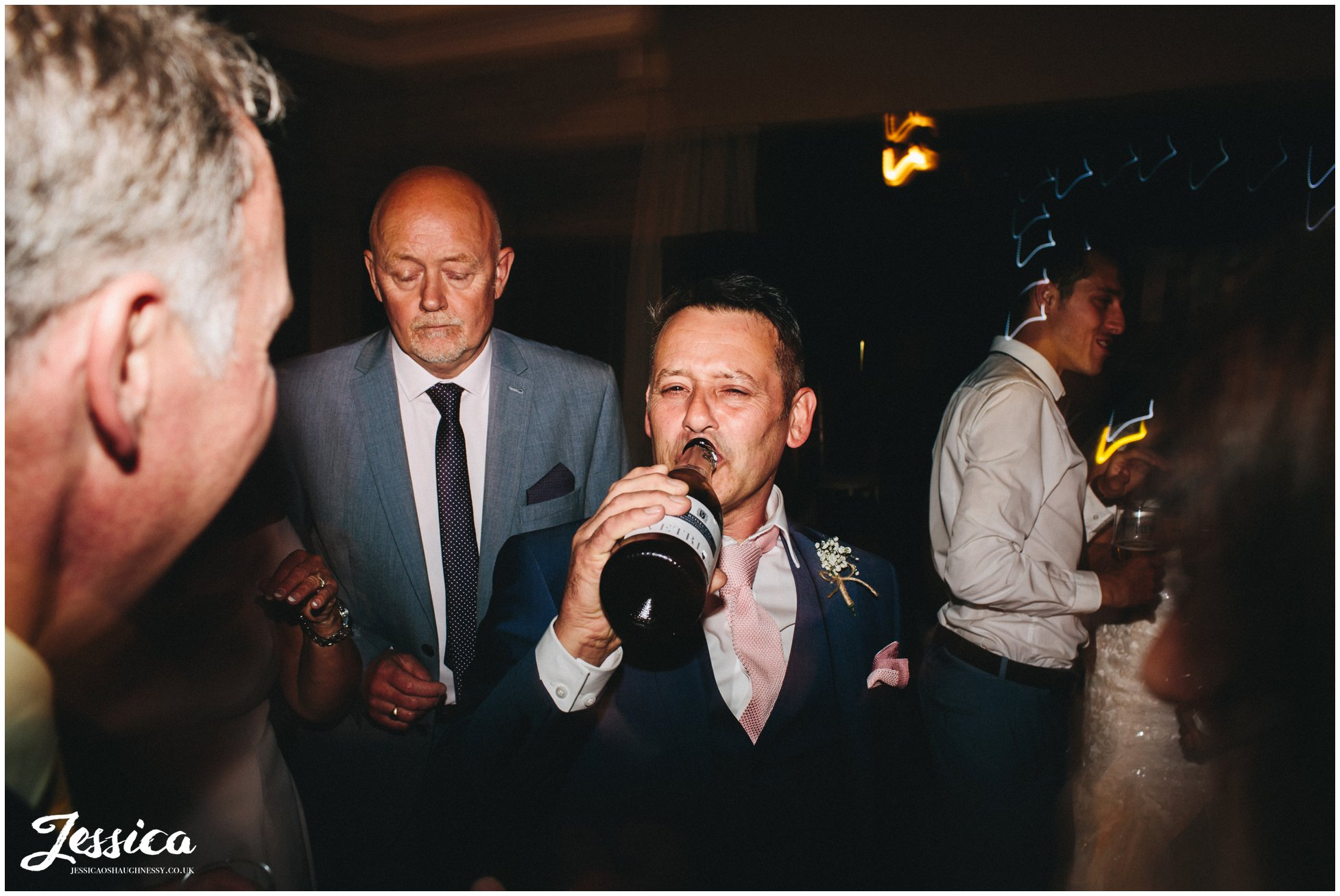 father of the bride drinks champagne out the bottle