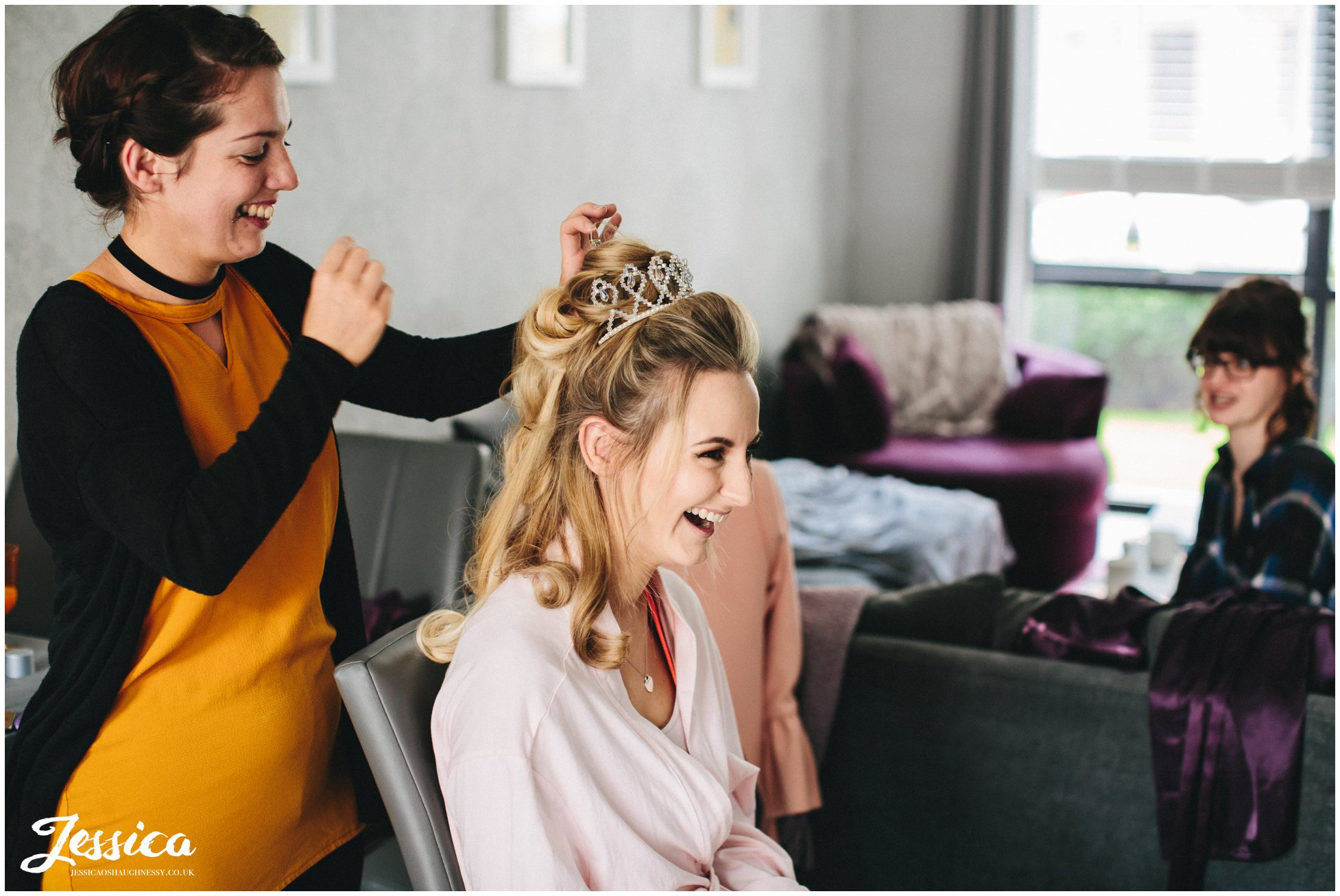 bride gets her hair done on the morning of her wedding