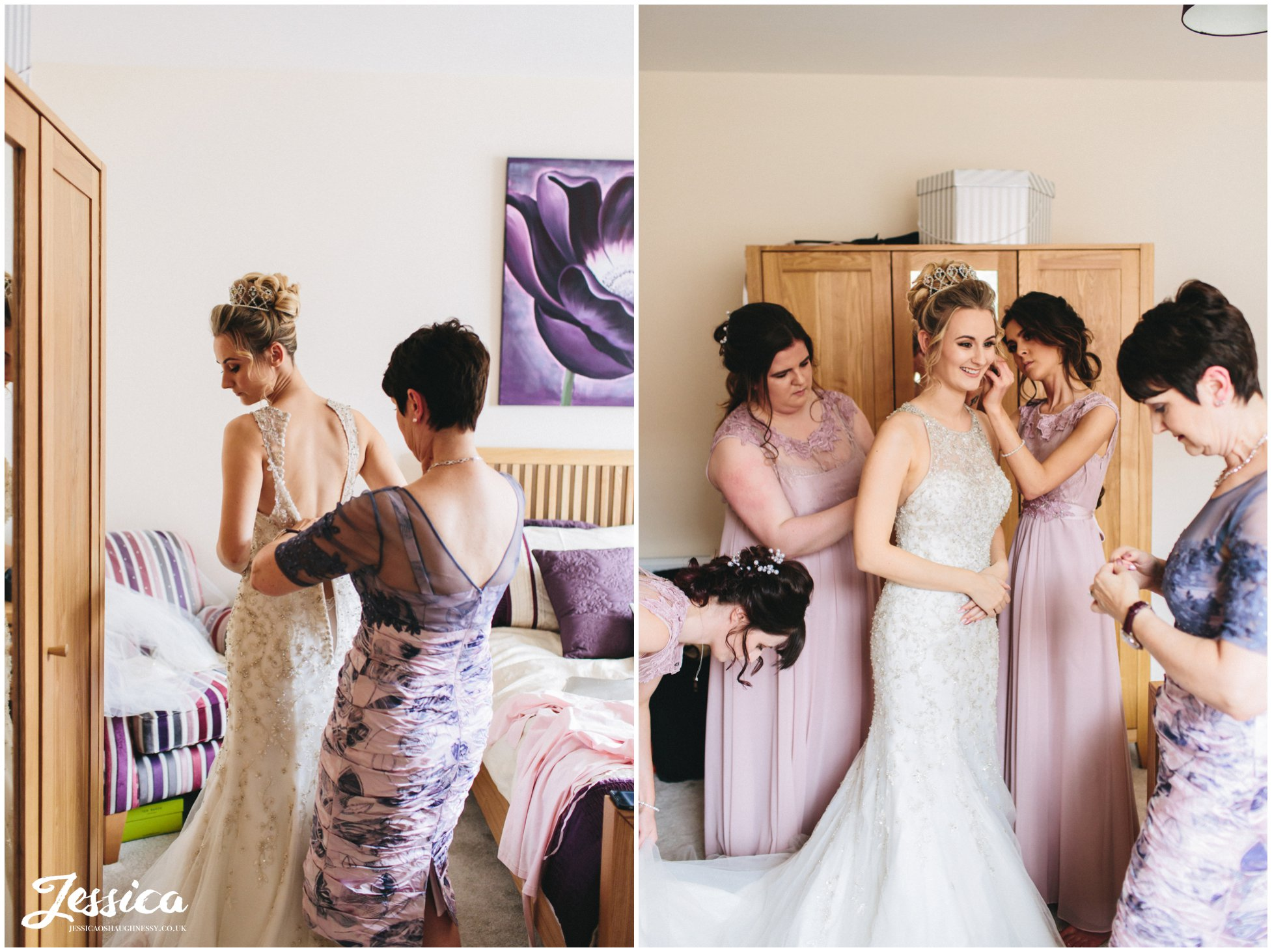 mother of the bride helps her daughter into her wedding dress