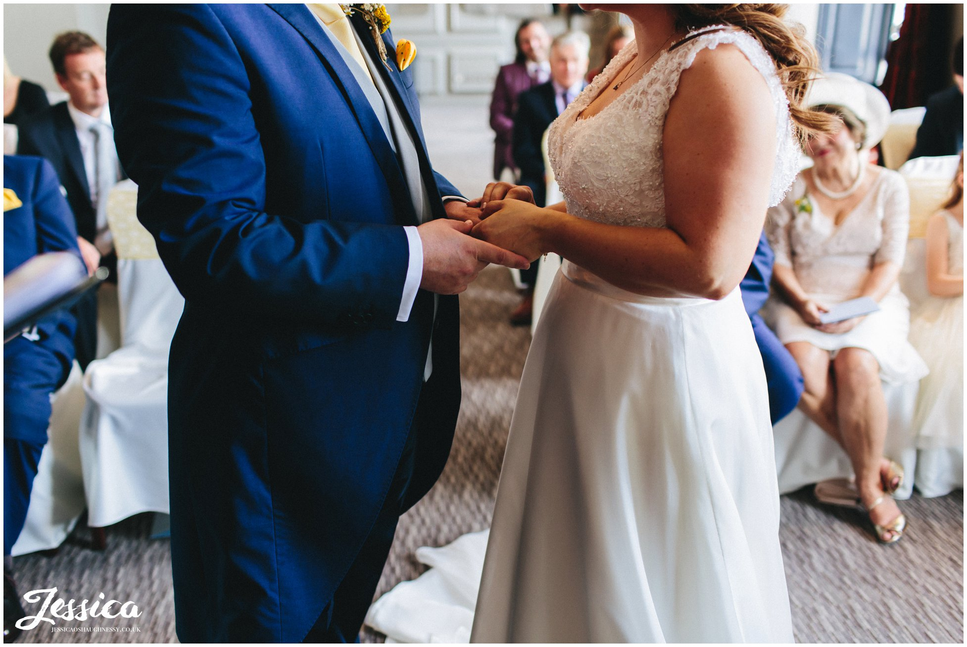 bride & groom hold hands during their wedding ceremony