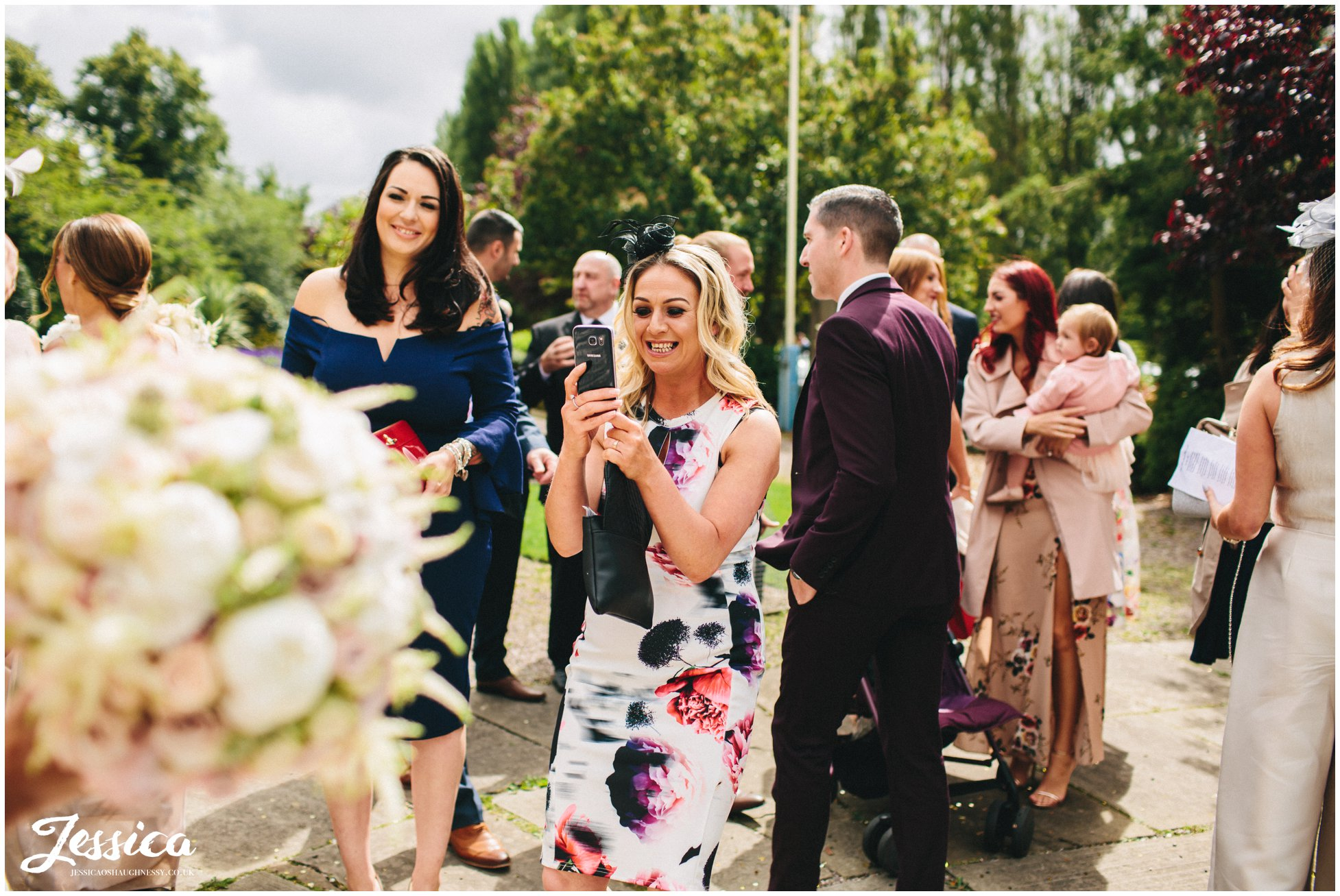 guests take photos of the bride after the wedding ceremony