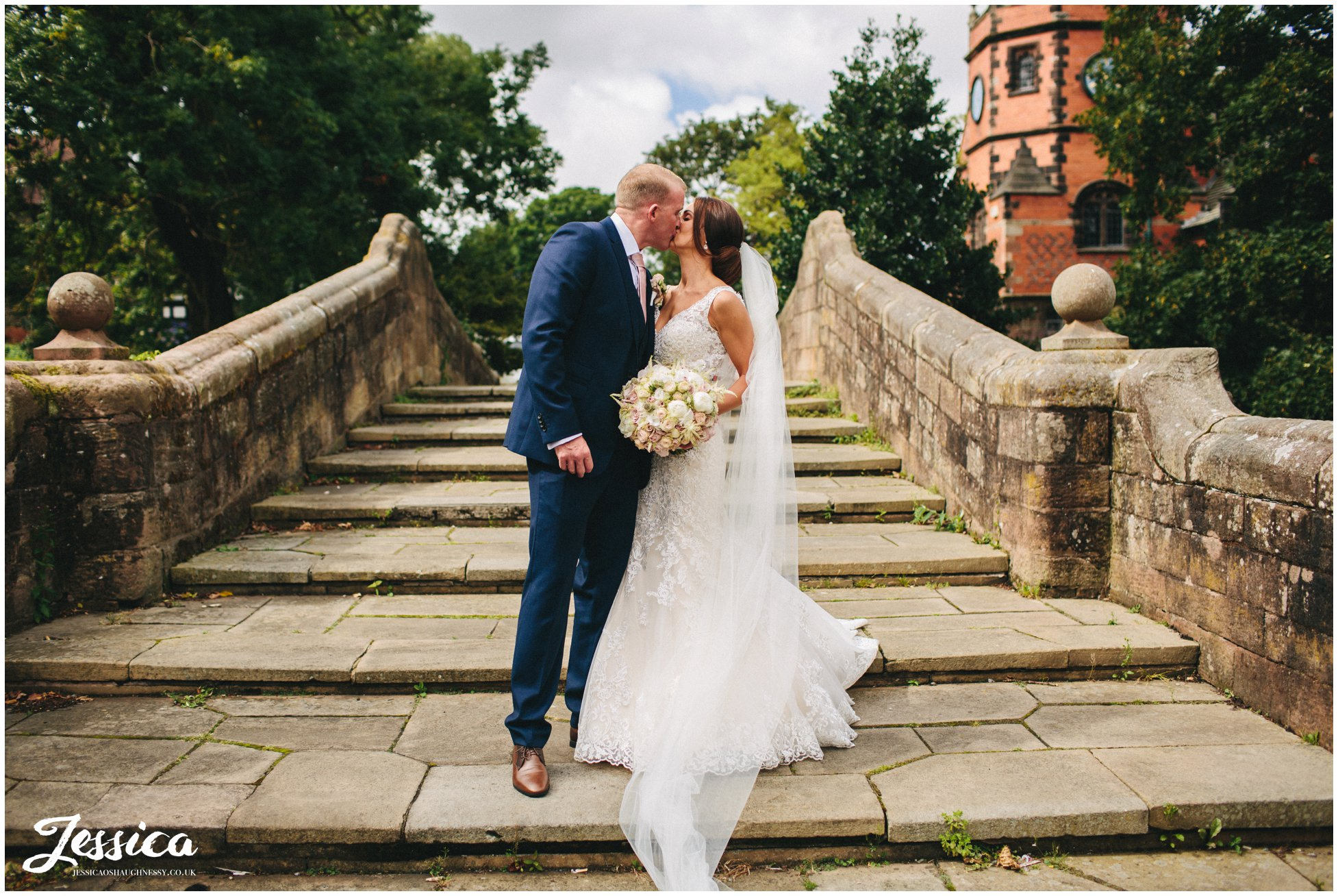 husband and wife kiss on the bridge in port sunlight