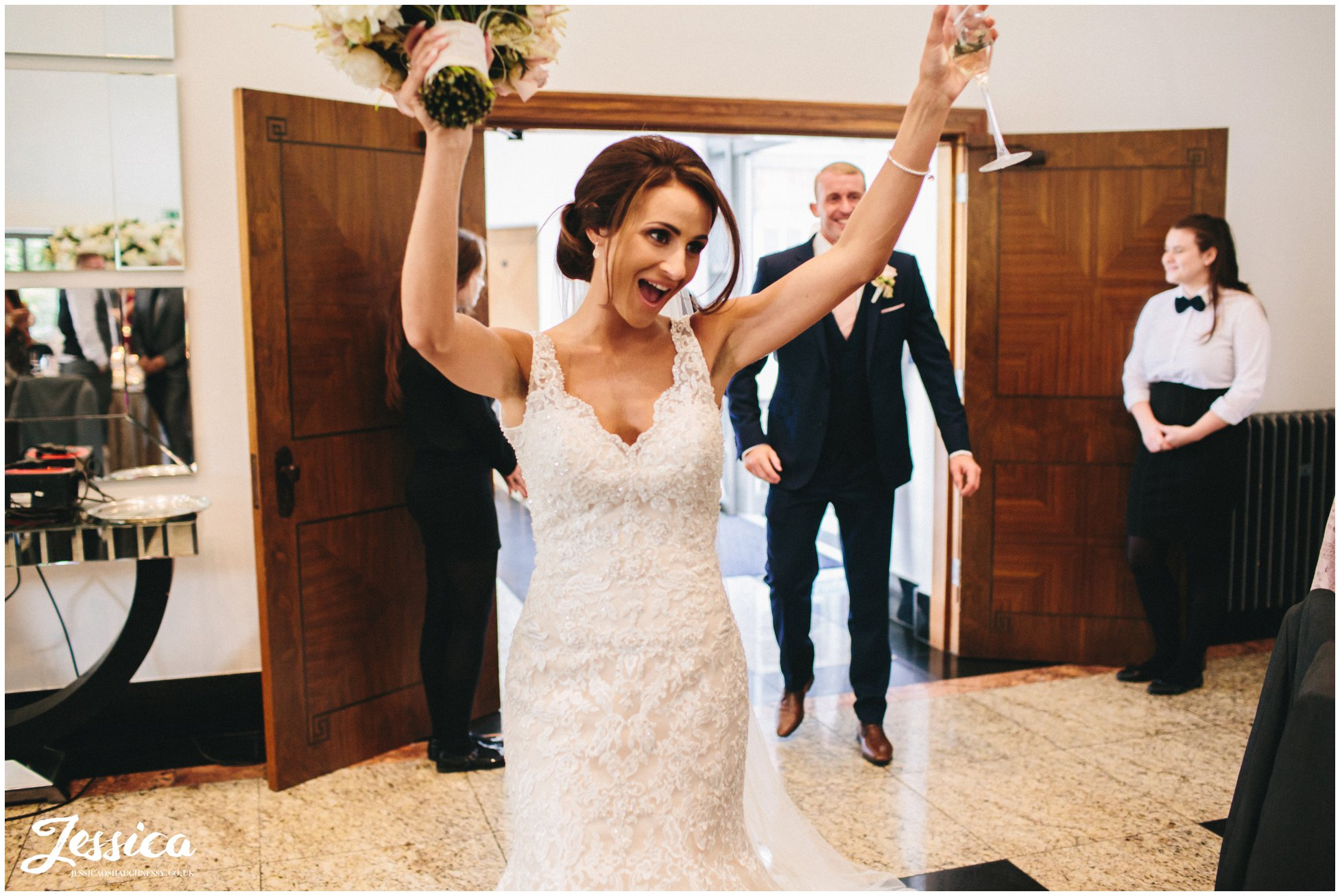 bride dances as she enters the room for the wedding breakfast