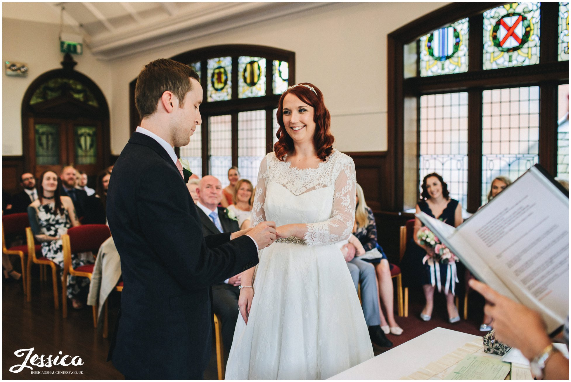 bride and groom exchange rings during their manchester wedding