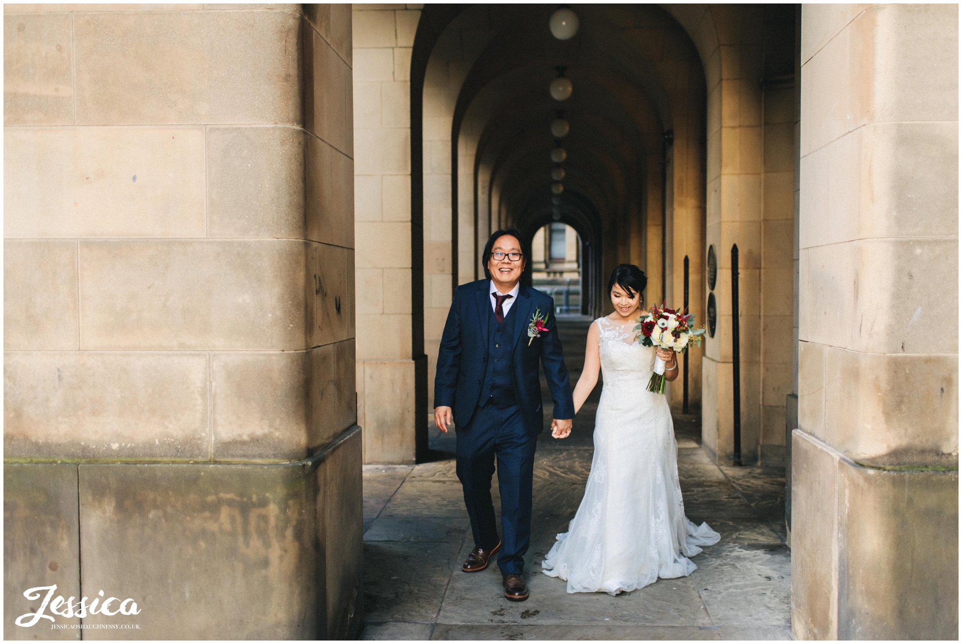 bride & groom walk the streets around manchester town hall