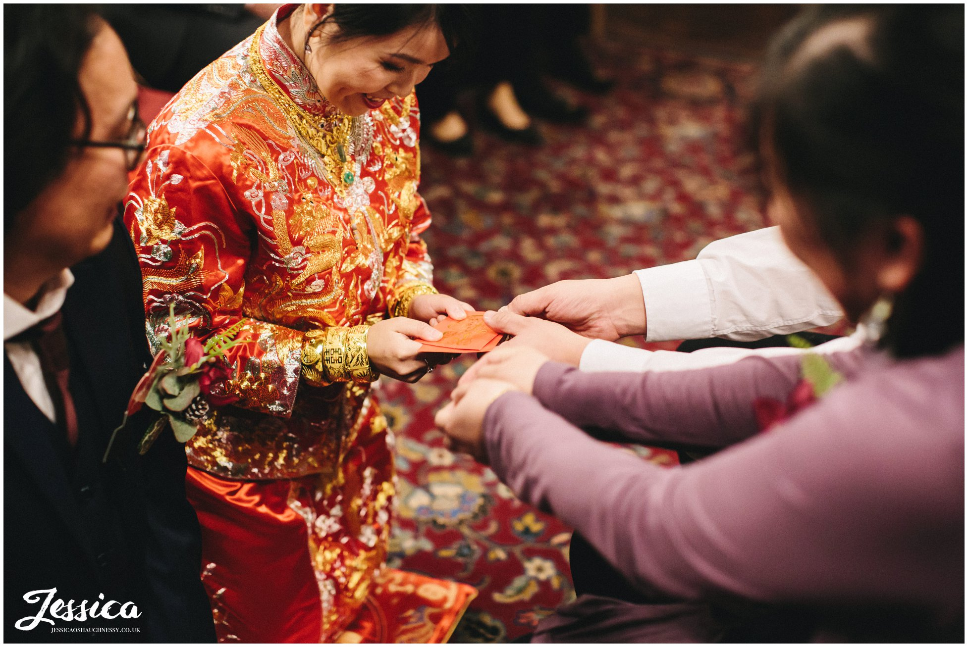 couple receive money from guests during the chinese tea ceremony