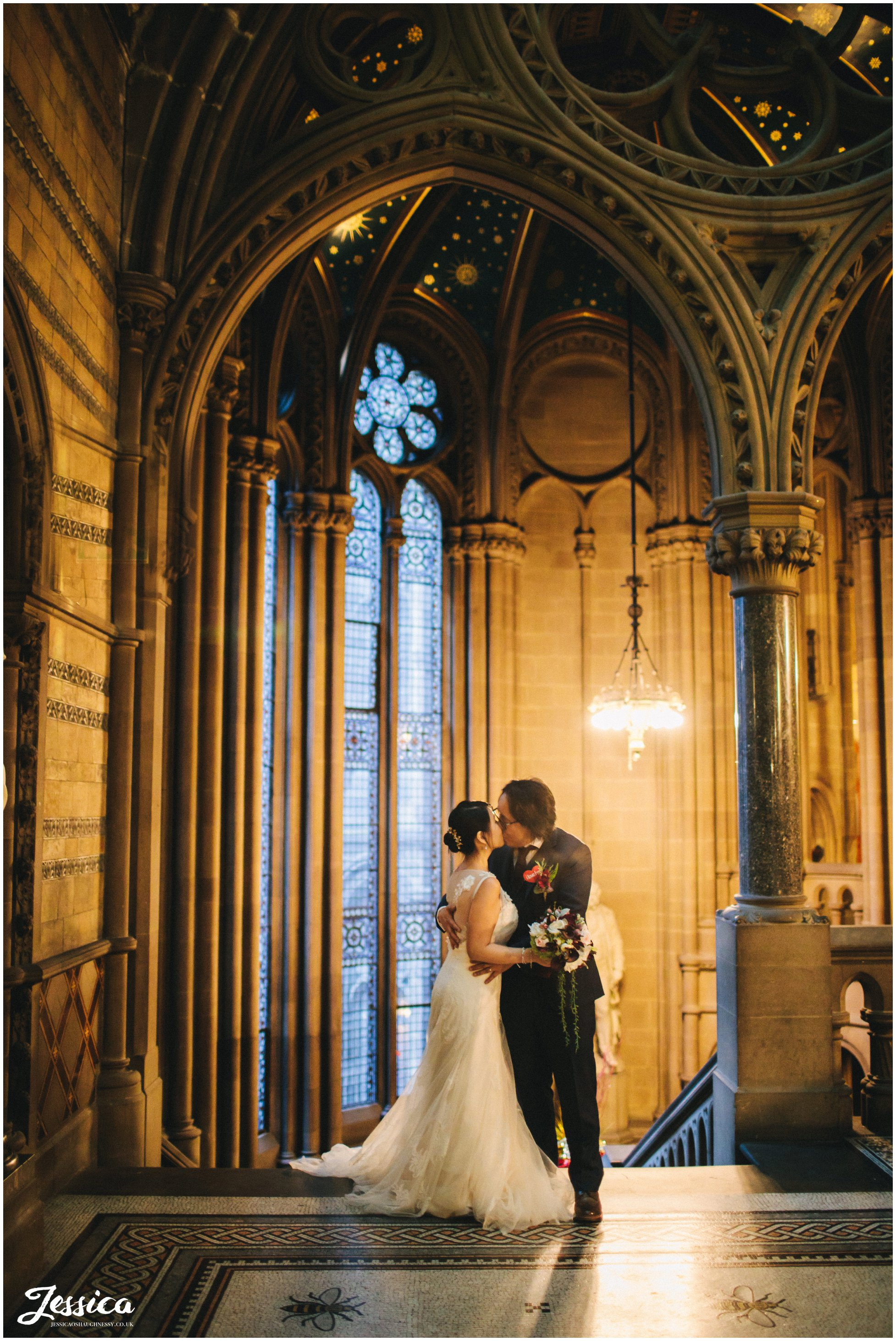 newly wed's kiss on the stairs of manchester town hall in the evening
