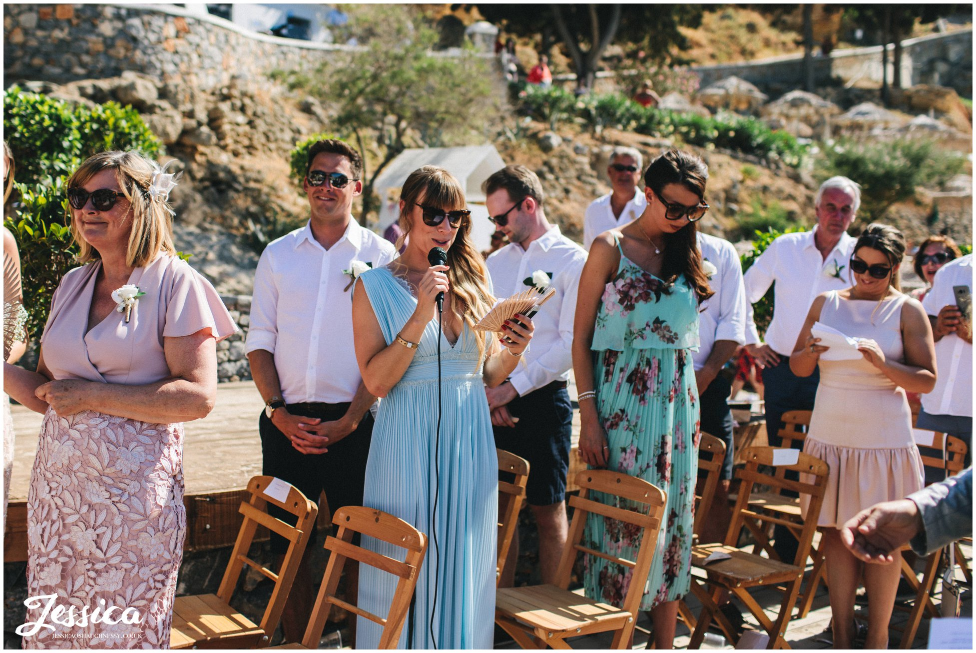 wedding guests give a reading during the ceremony in greece