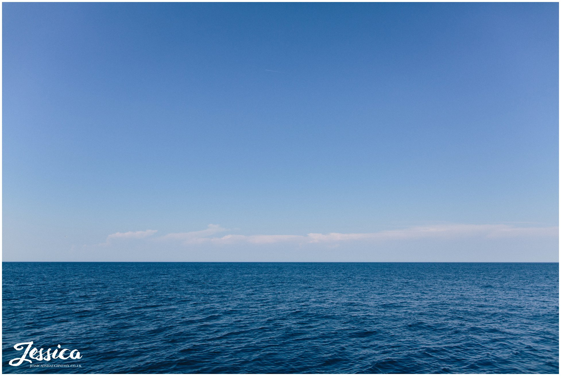 a photograph of the blue sky & sea
