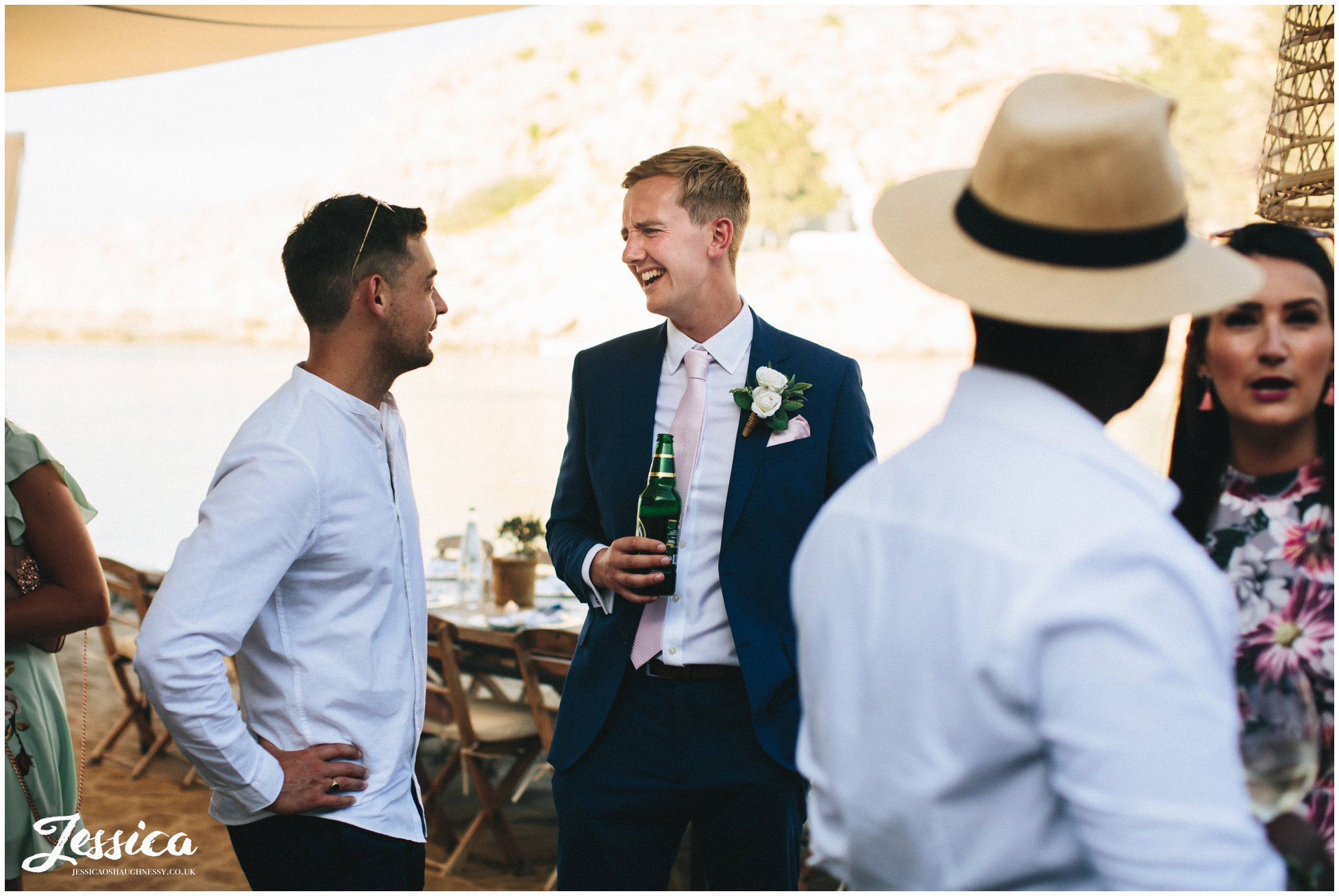 the groom jokes with his friends at their wedding reception