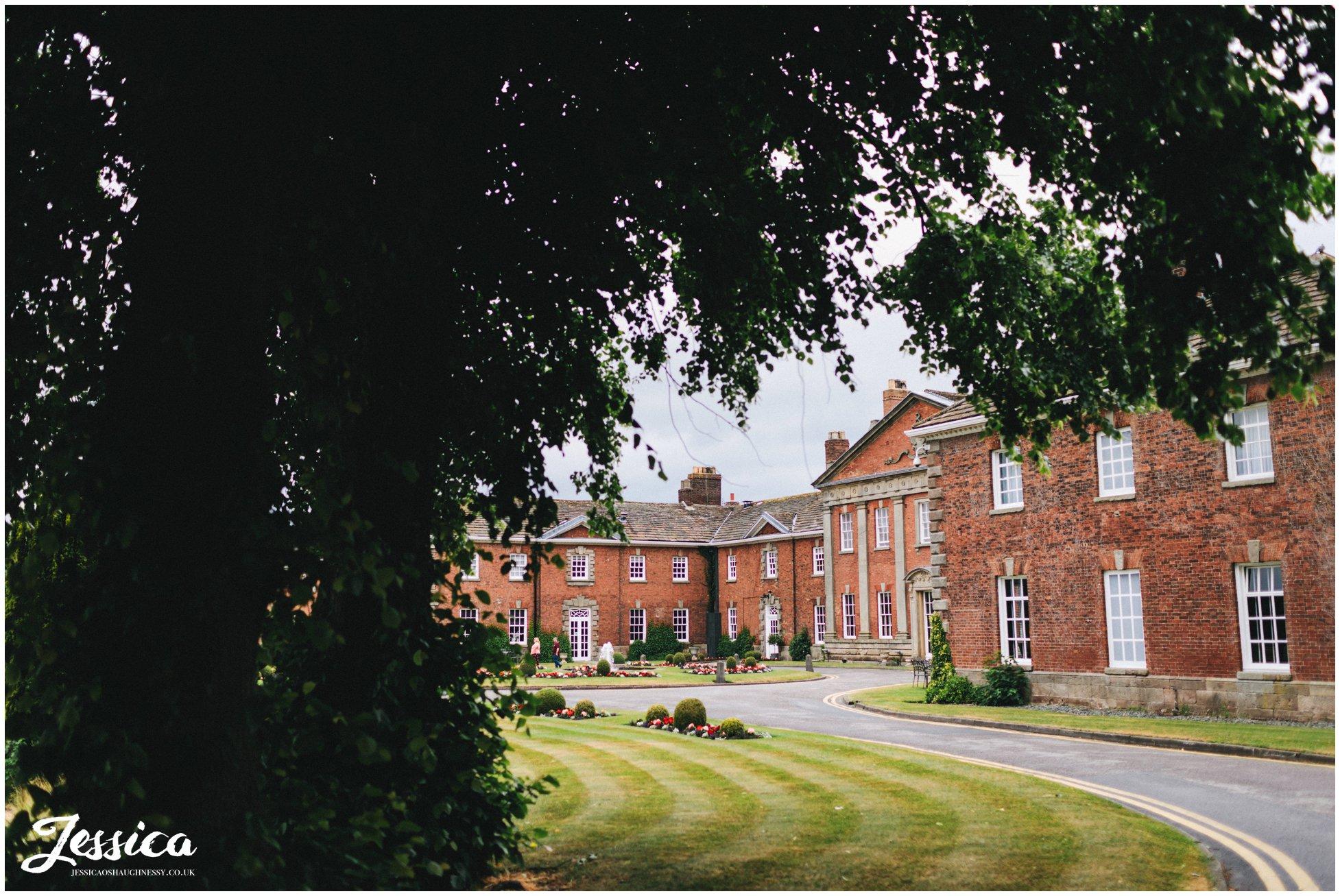 photograph of Mottram Hall through the trees