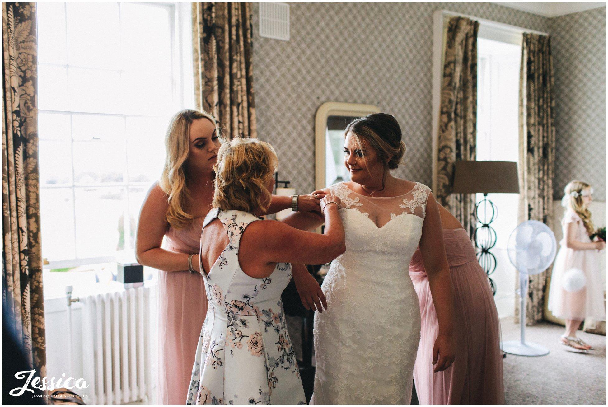 bridesmaids help the bride into her wedding dress at mottram hall