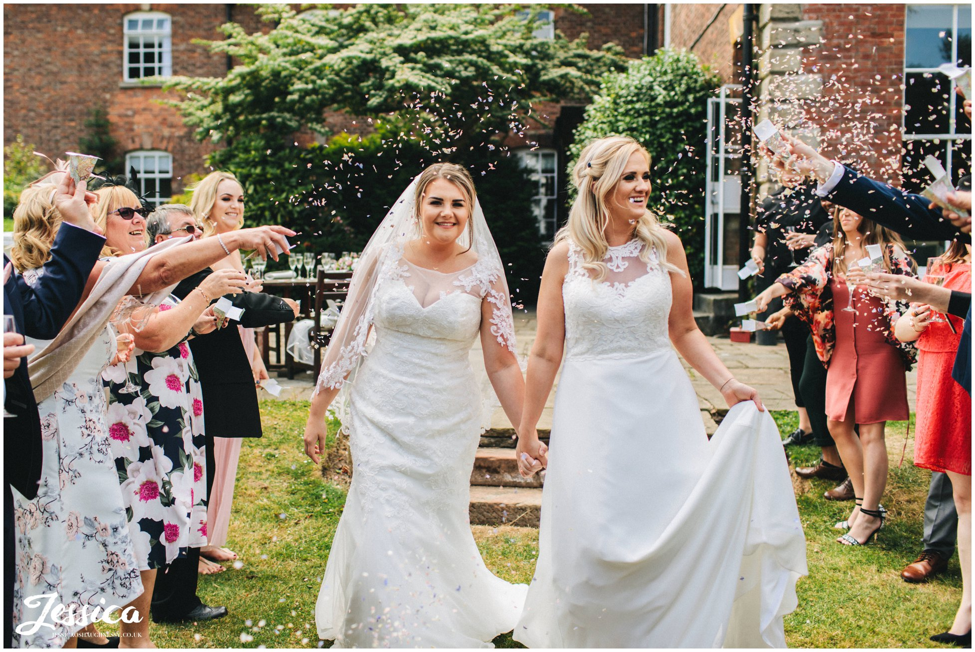 guests throw confetti over the brides as they walk through