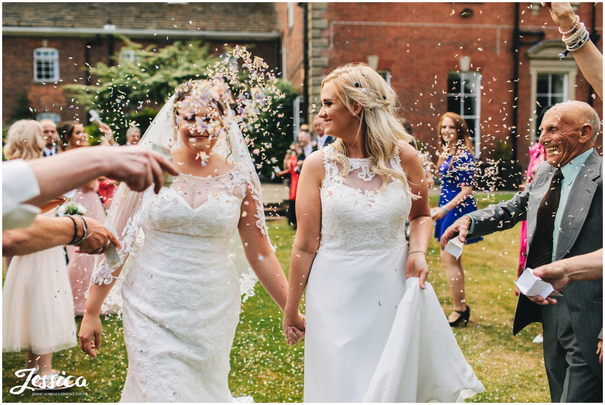 a guest covers one of the brides in confetti