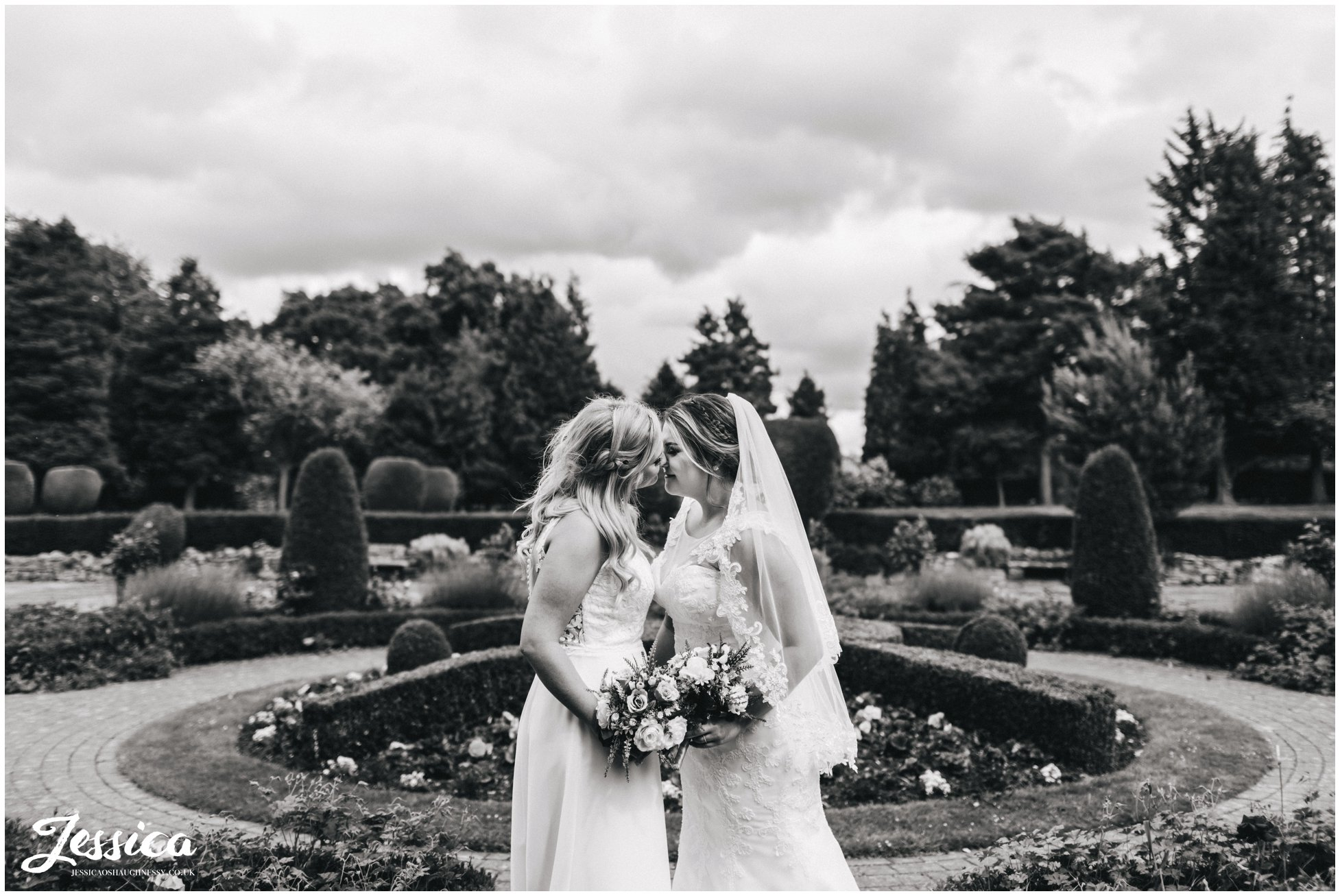 black & white photo of the two brides kissing on their weddind day