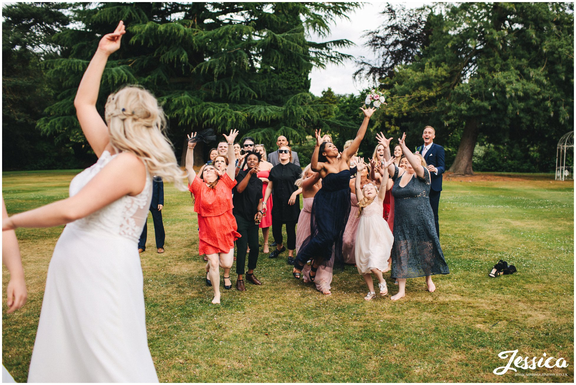 the brides throw their bouquets to their single wedding guests
