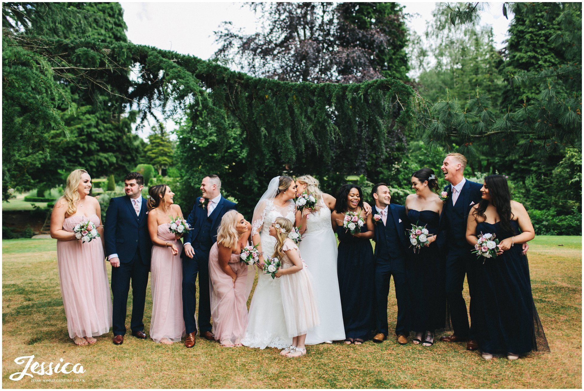 brides & their wedding party laugh together in the gardens